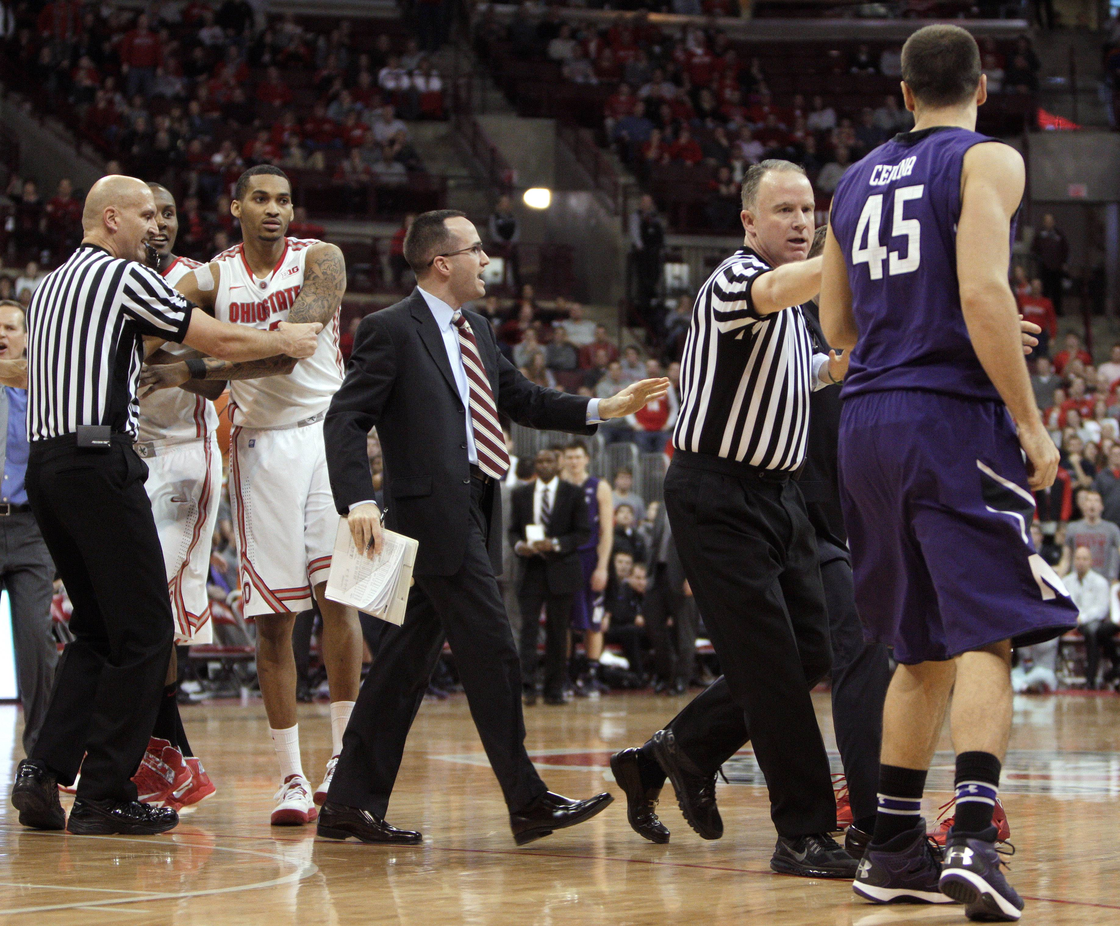 Referees and coaches separate Northwestern's Nikola Cerina (45) and Ohio State's LaQuinton Ross during a second-half scuffle in an NCAA college basketball game Wednesday, Feb. 19, 2014, in Columbus, Ohio. Cerina and Ross were both ejected from the game. Ohio State defeated Northwestern 76-60. (AP Photo/Jay LaPrete)