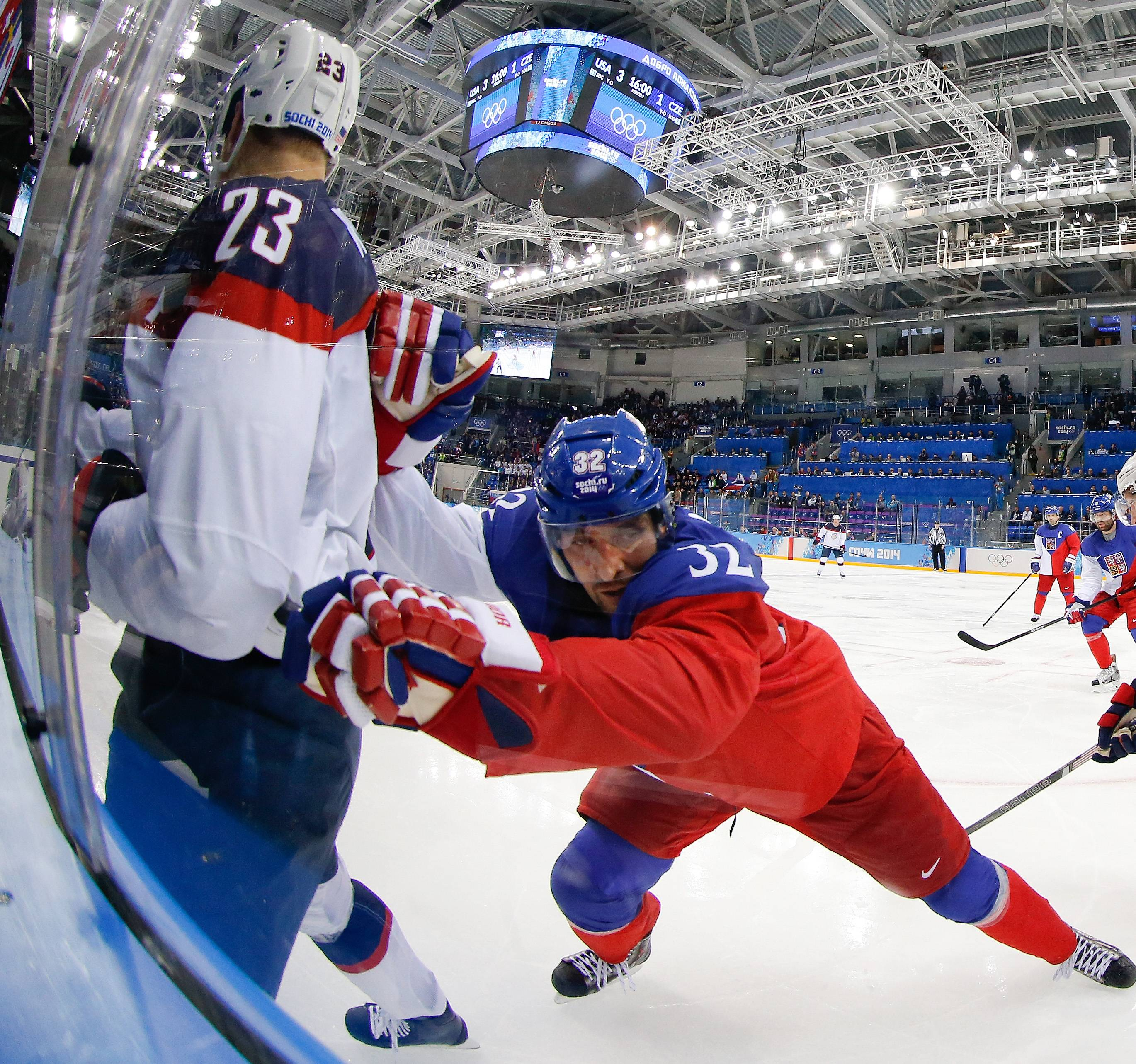 Czech Republic defenseman Michal Rozsival pins USA forward Dustin Brown agains the glass during the second period of men's quarterfinal hockey game.