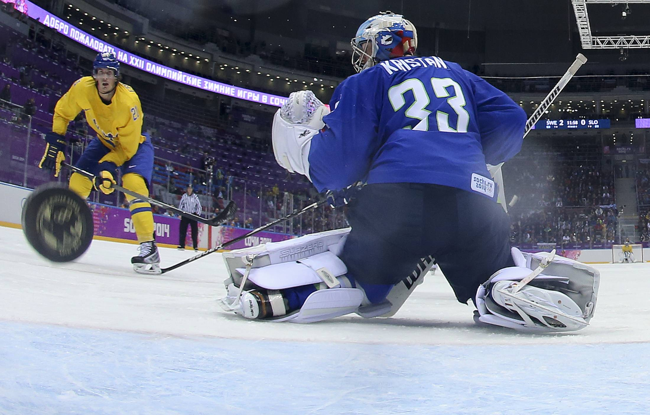 Sweden forward Loui Eriksson shoots and scores against Slovenia goaltender Robert Kristan in the third period of a men's ice hockey game at the 2014 Winter Olympics, Wednesday, Feb. 19, 2014, in Sochi, Russia. Sweden won 5-0 to advance to the semifinals. (AP Photo/Martin Rose, Pool)