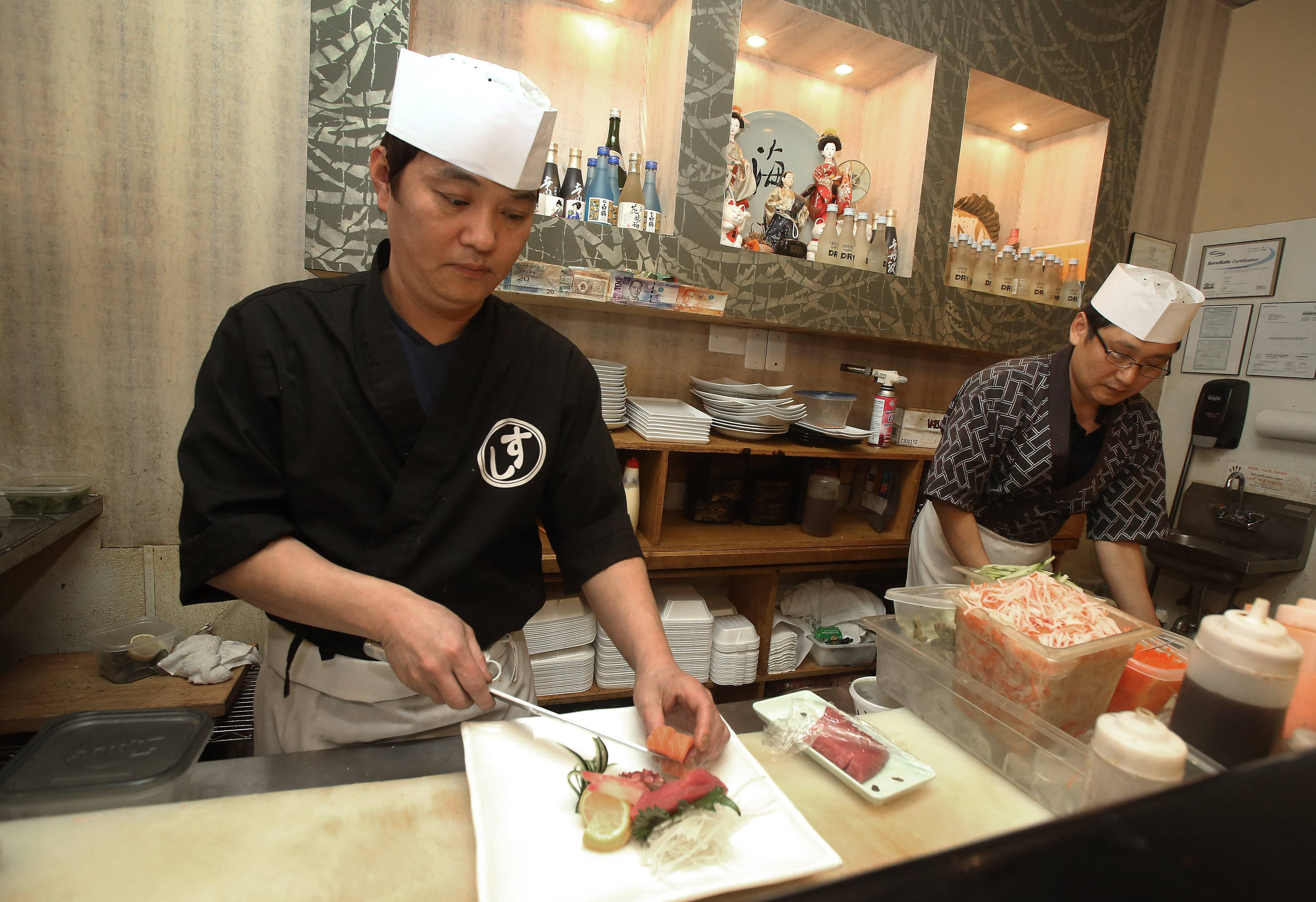Head chef John Chun, left, and first chef Sean Jun create sushi rolls Hayashi Japanese Restaurant in Gurnee.