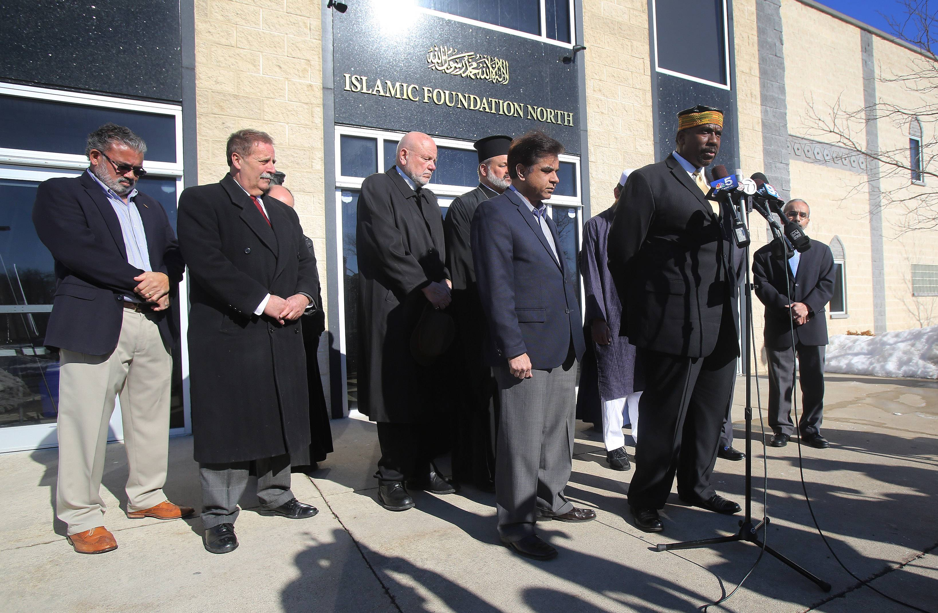 Imam Matthew Ramadan of the Council of Islamic Organizations of Greater Chicago joins other religious leaders in prayer at Islamic Foundation North during a news conference Wednesday to discuss vandalism of St. Demetrios Greek Orthodox Church and Islamic Foundation North in Waukegan. The graffiti was discovered at the church and mosque early Monday.
