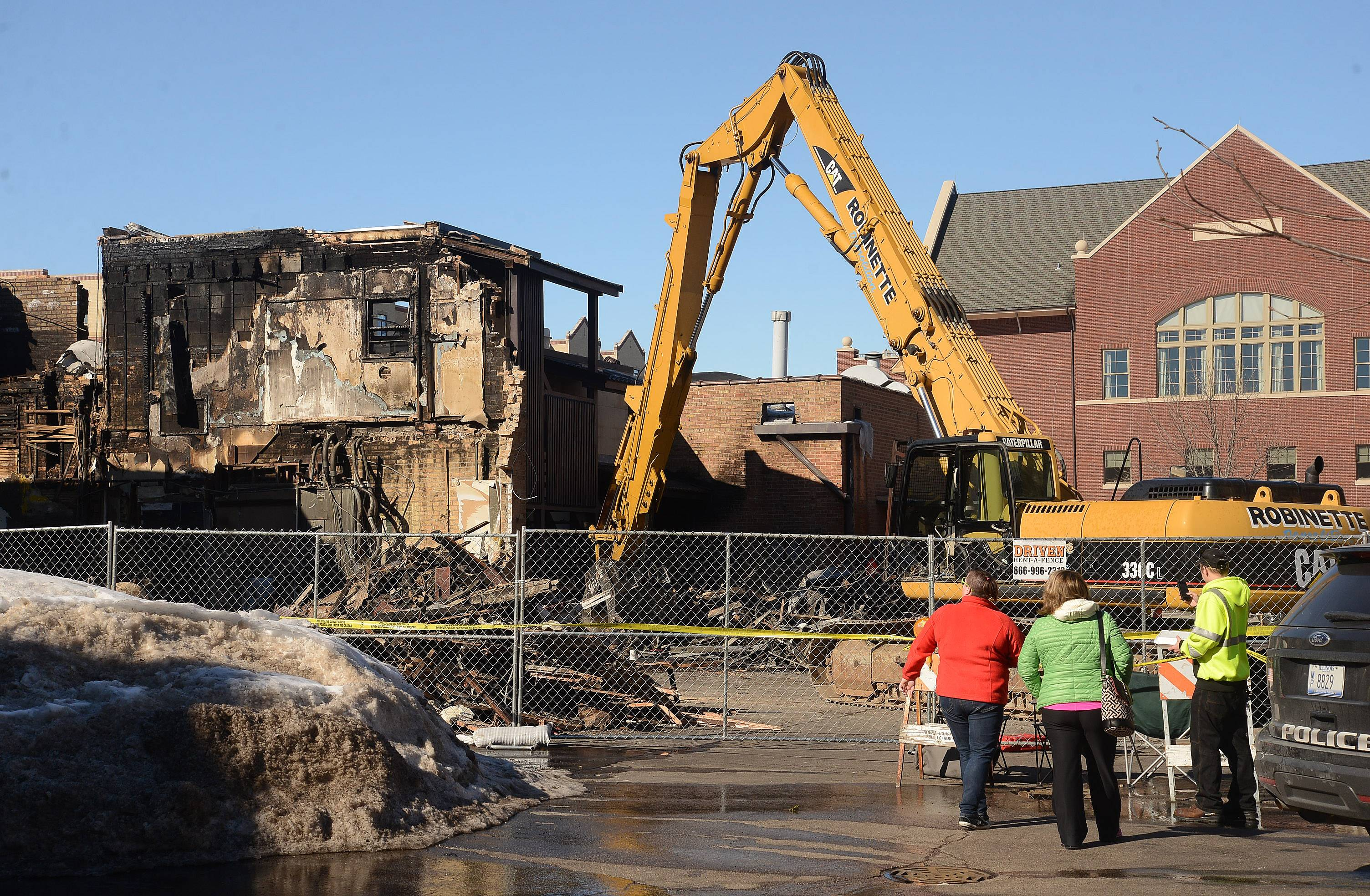 From left, Allison Haynes, Lisa Haynes and John Haynes check out the ongoing demolition of 105 S. Main St. in downtown Mount Prospect. Lisa Haynes lives in one of the original Busse homes that once stood where the Continental Bakery is now.