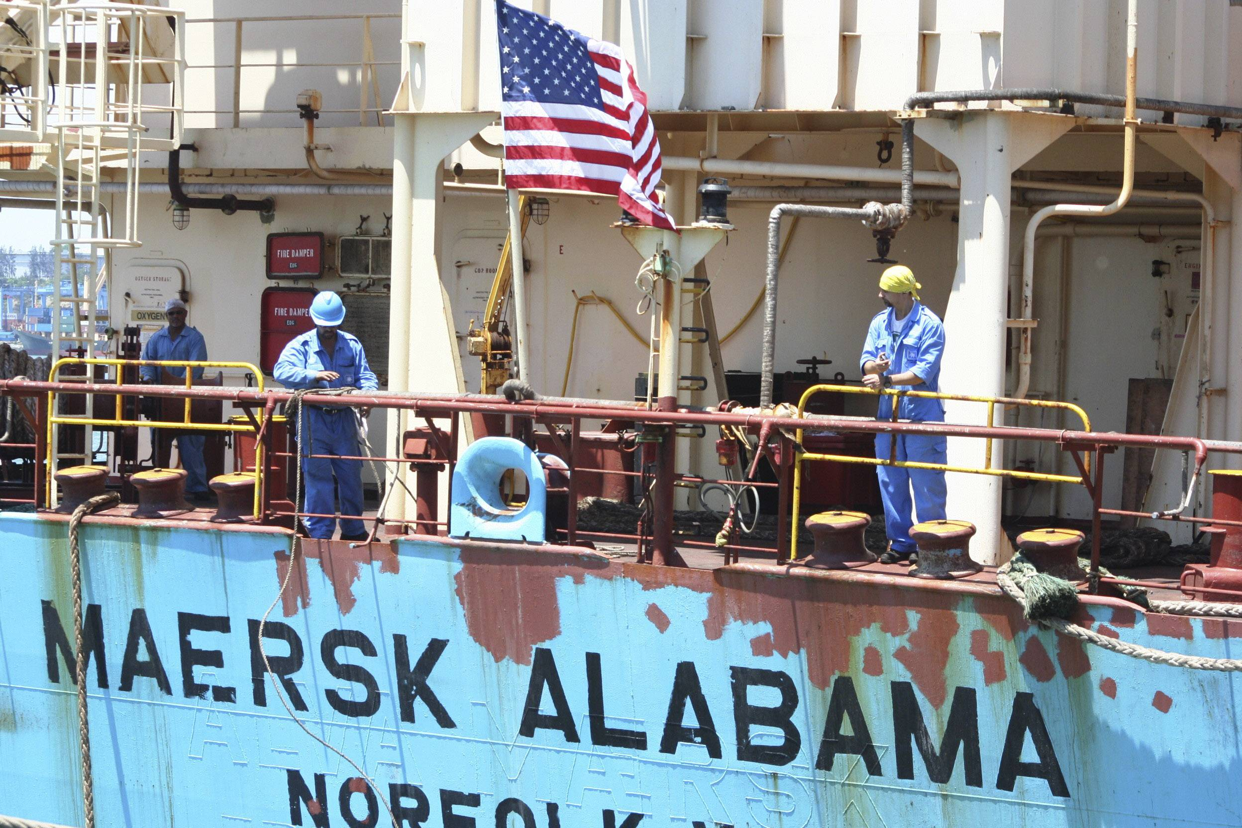 Crew members work aboard the U.S.-flagged Maersk Alabama after the ship docked in the harbour of Mombasa, Kenya, in this Nov. 22, 2009 file photo. Police in the Indian Ocean island nation of Seychelles said Wednesday that two American security officers were found dead Tuesday in a cabin on the Maersk Alabama.