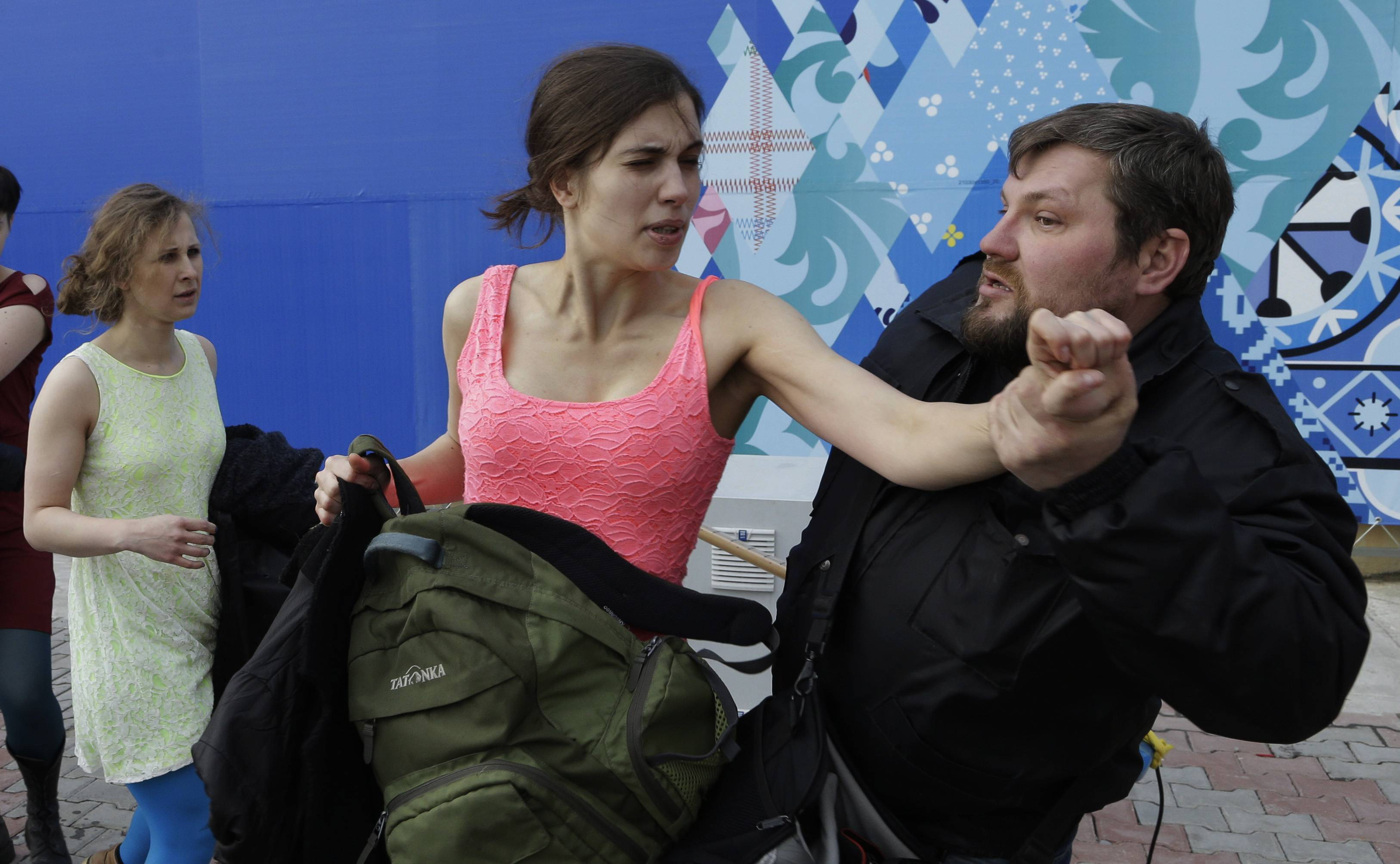 A Russian security officer attacks Nadezhda Tolokonnikova and a photographer as she and fellow members of the punk group Pussy Riot, including Maria Alekhina, left, stage a protest performance in Sochi, Russia, Wednesday.