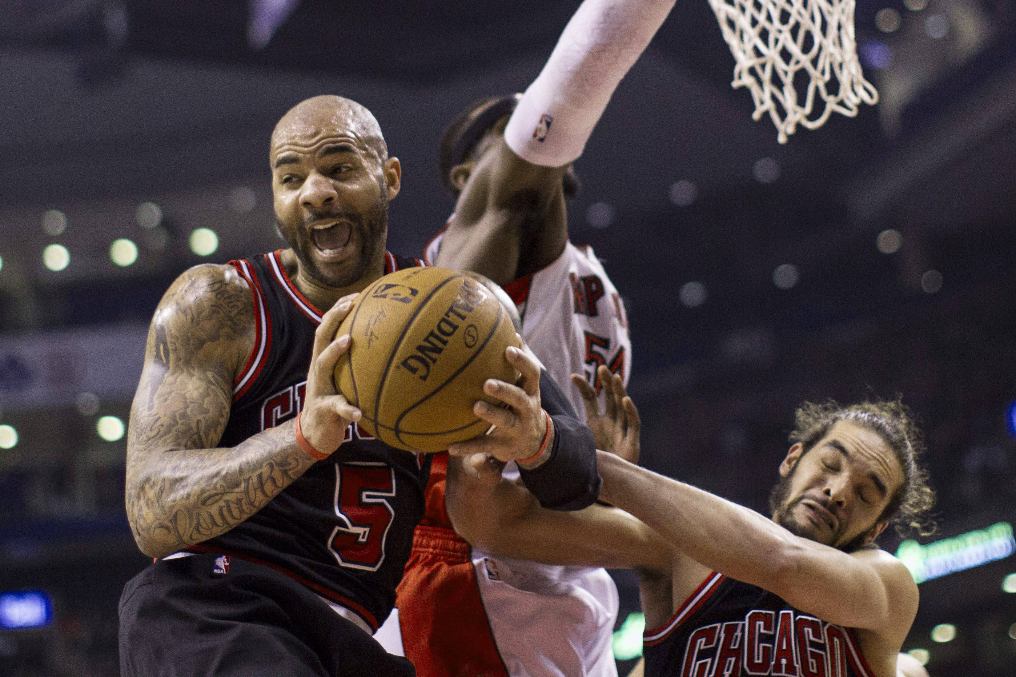 Chicago Bulls' Carlos Boozer (5) claims a rebound in front of Toronto Raptors' Patrick Patterson and Bulls' Joakim Noah during the first half of an NBA basketball game, Wednesday, Feb. 19, 2014 in Toronto.