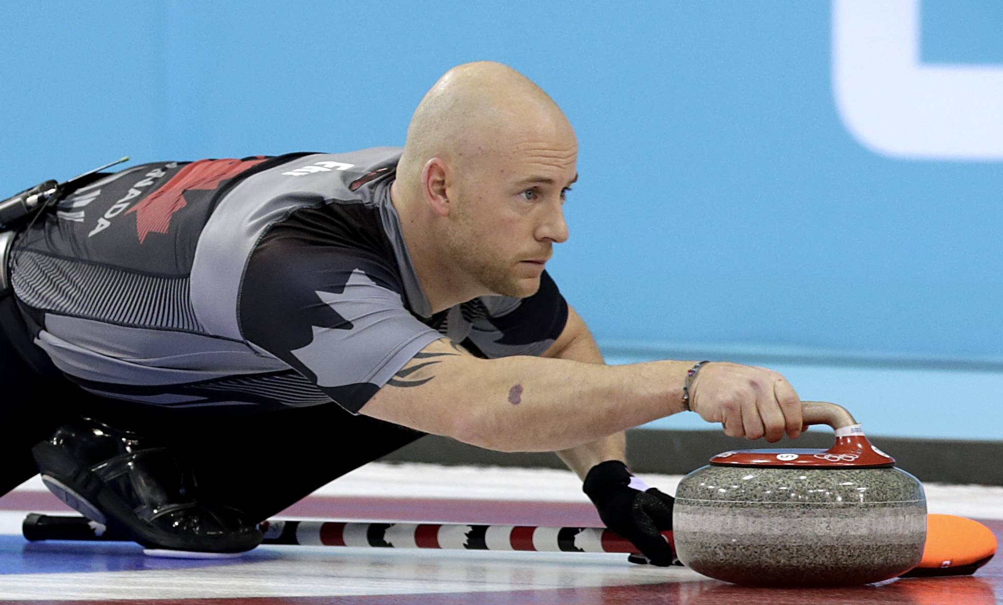 Canada's Ryan Fry delivers the rock during the men's curling semifinal game.