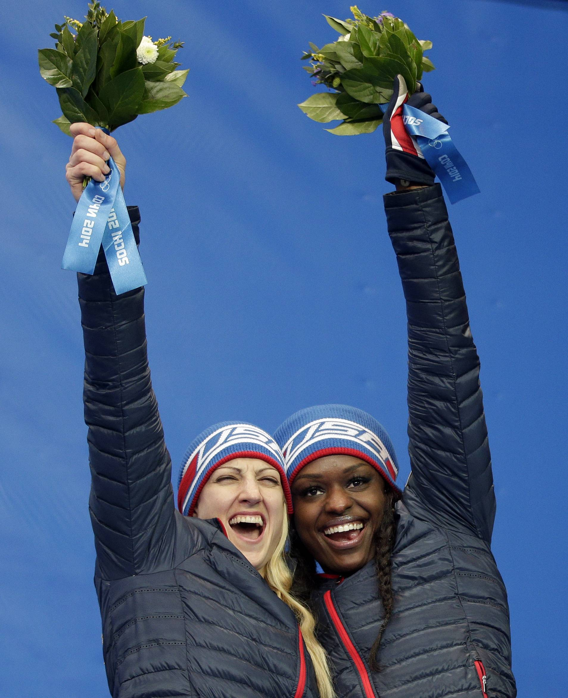 Bronze medal winners from the United States Jamie Greubel and Aja Evans pose during the flower ceremony for the women's bobsled competition.