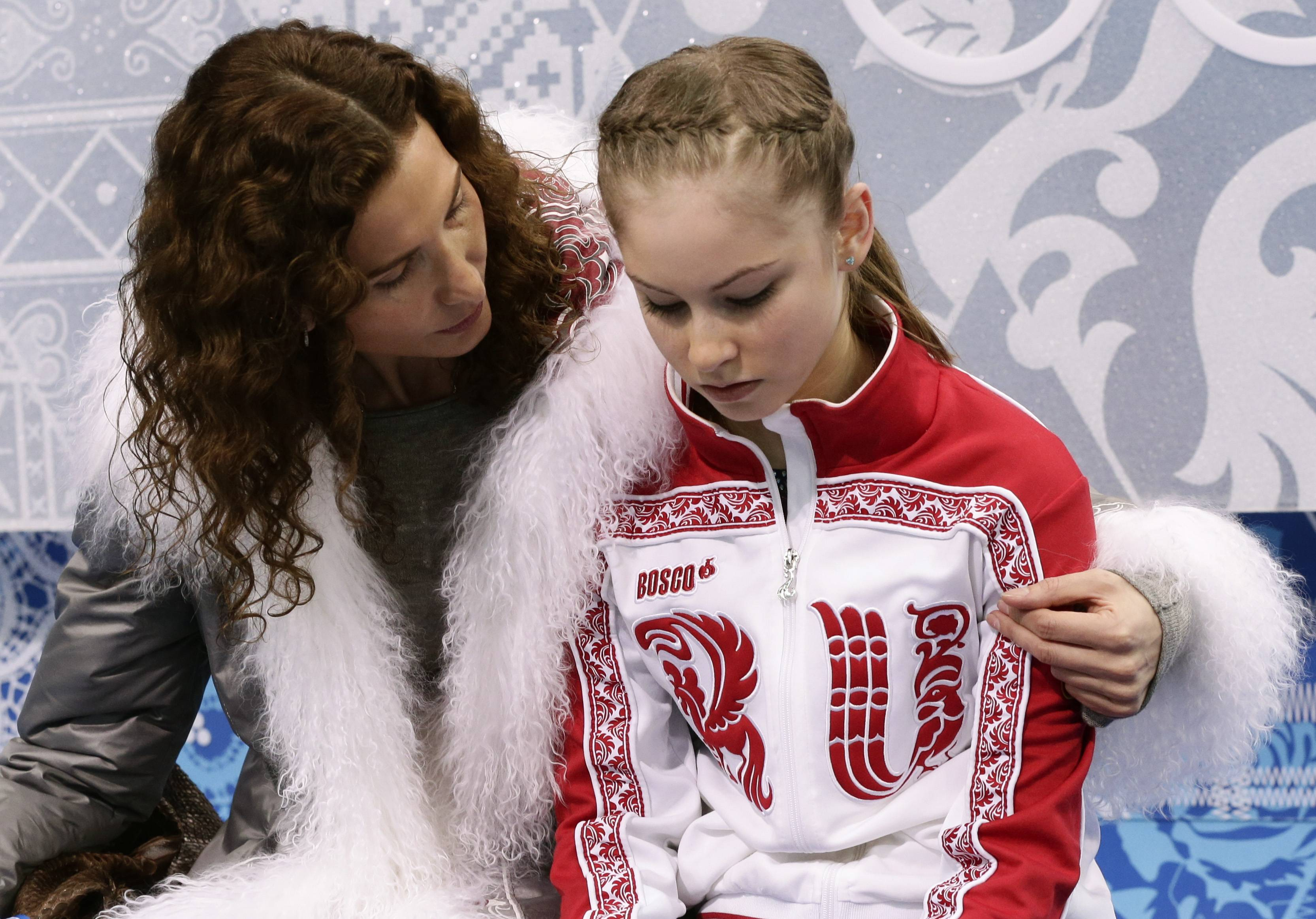 Julia Lipnitskaya of Russia, right, and her coach Eteri Tutberidze wait in the results area after she completed her routine in the women's short program figure skating competition.