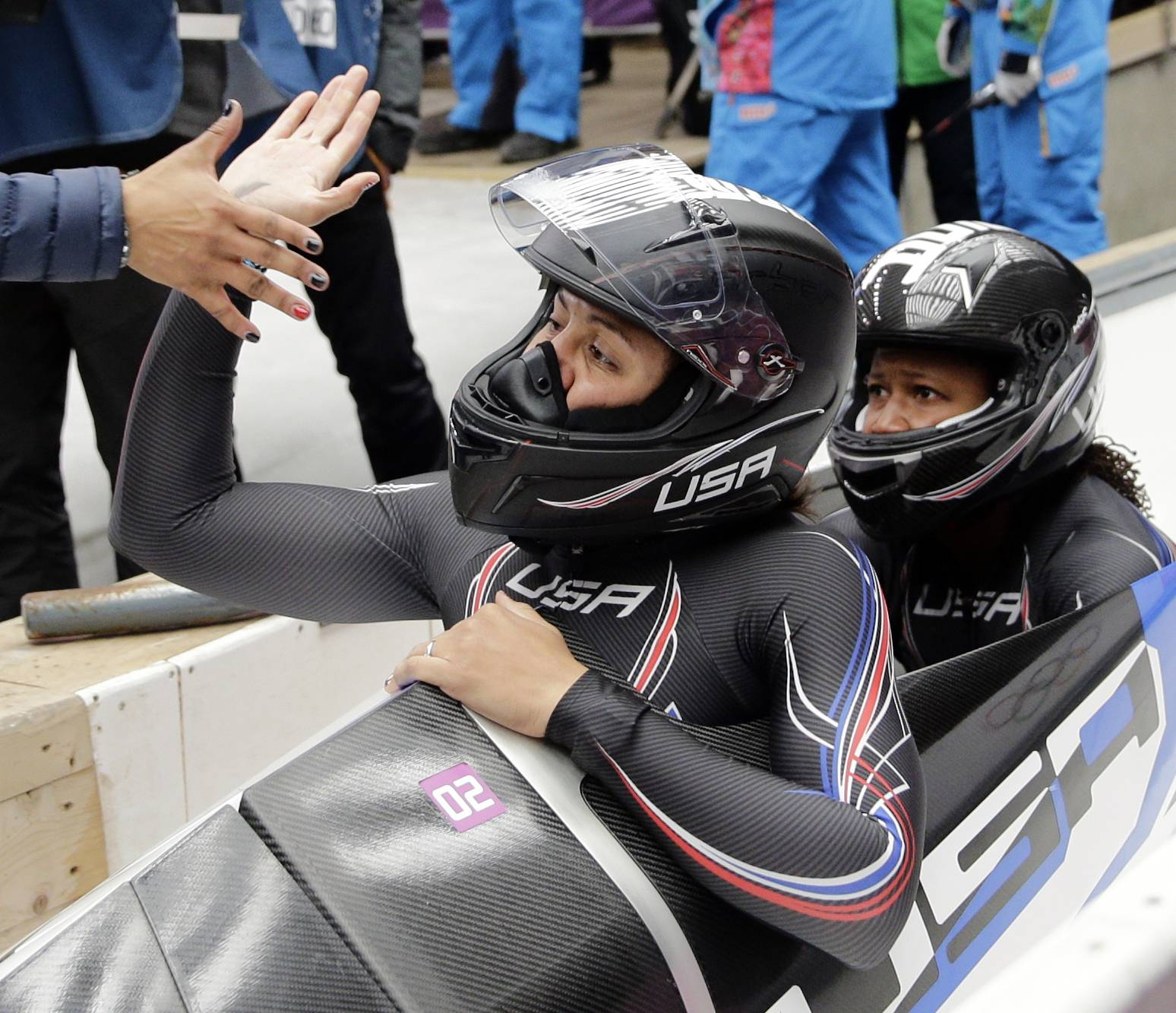 The team from the United States USA-1, piloted by Elana Meyers with brakeman Lauryn Williams, get congratulated in the finish area after their silver medal run.