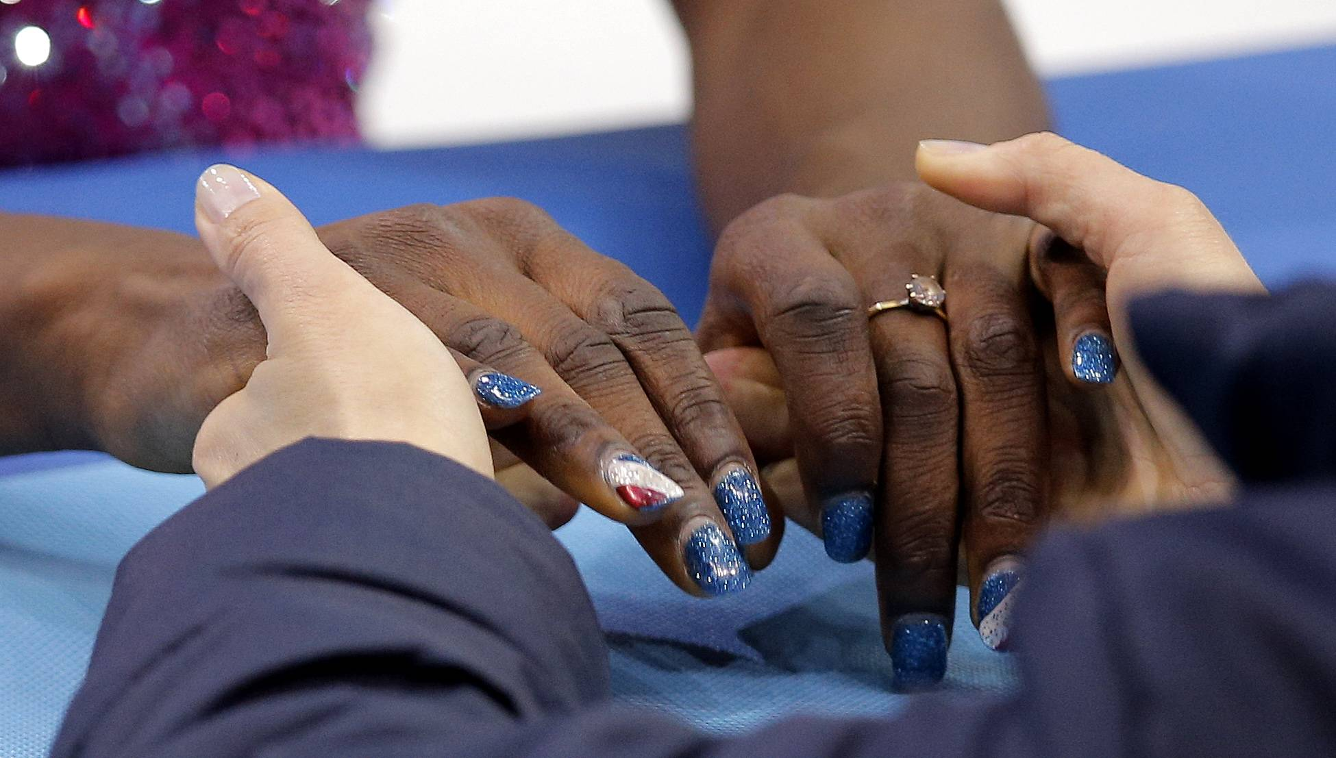 The hands of Mae Berenice Meite of France are seen as she talks to her coach before competing in the women's short program figure skating competition.