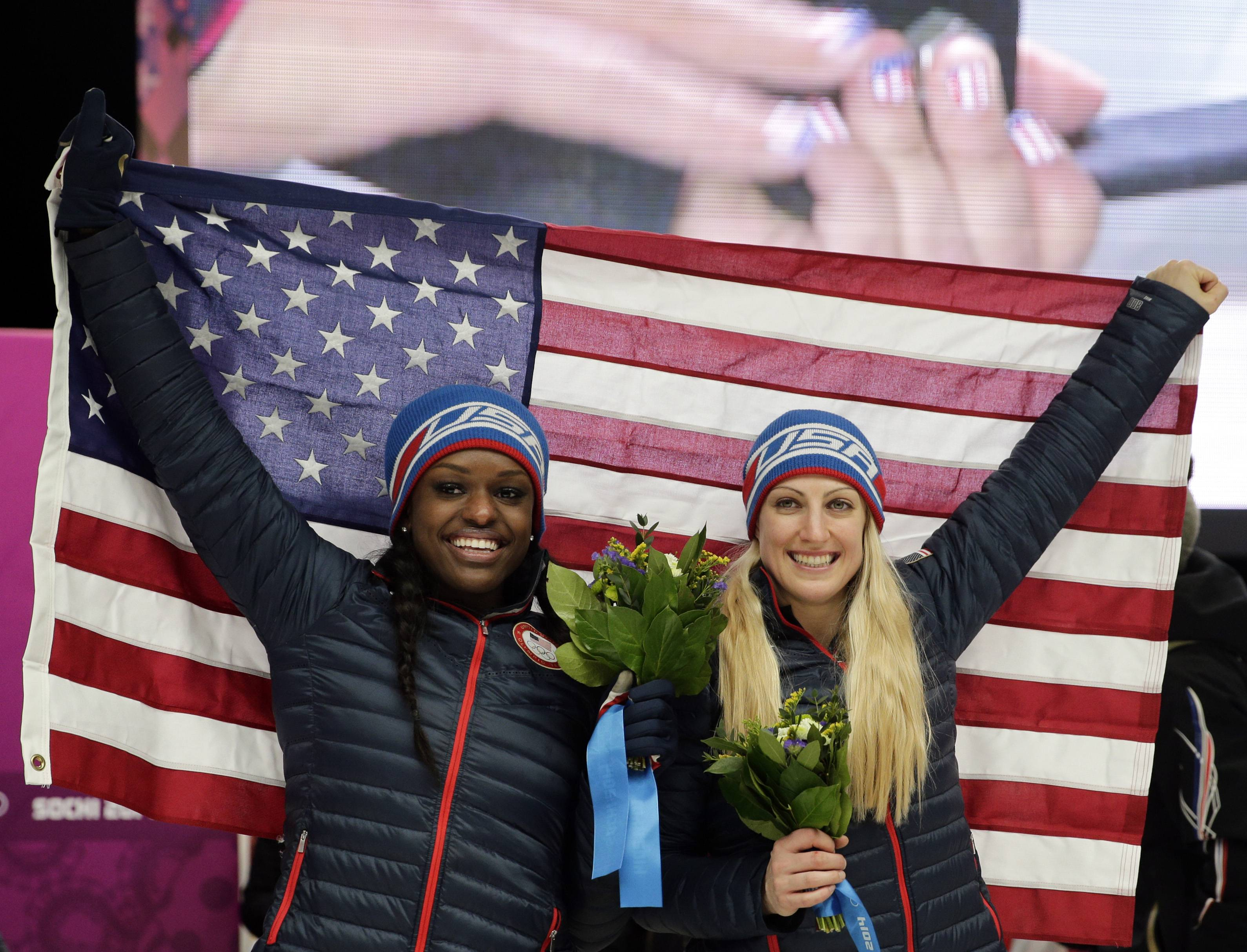 Bronze medal winners from the United States Jamie Greubel and Aja Evans, left, pose for pictures after the women's bobsled competition.