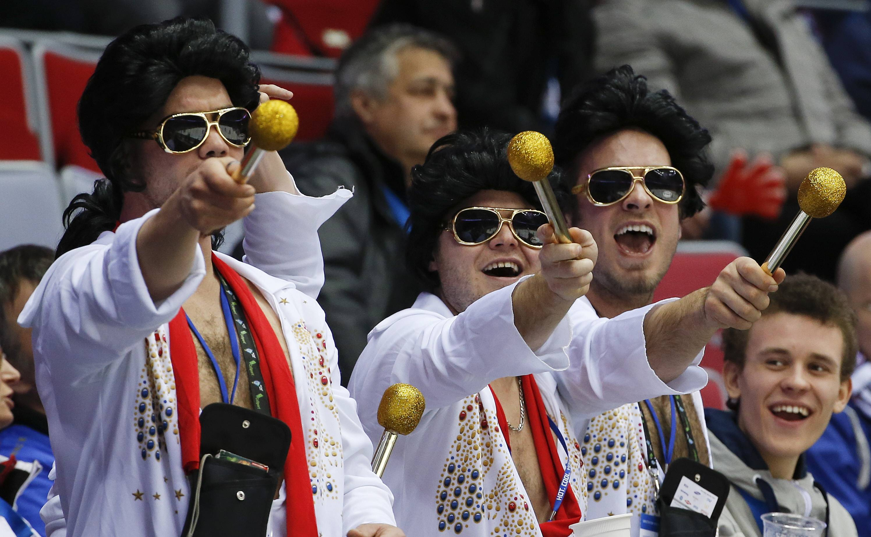 Hockey fans dressed as Elvis entertain other fans during a break in play during the third period of a men's quarterfinal ice hockey game between Canada and Latvia.