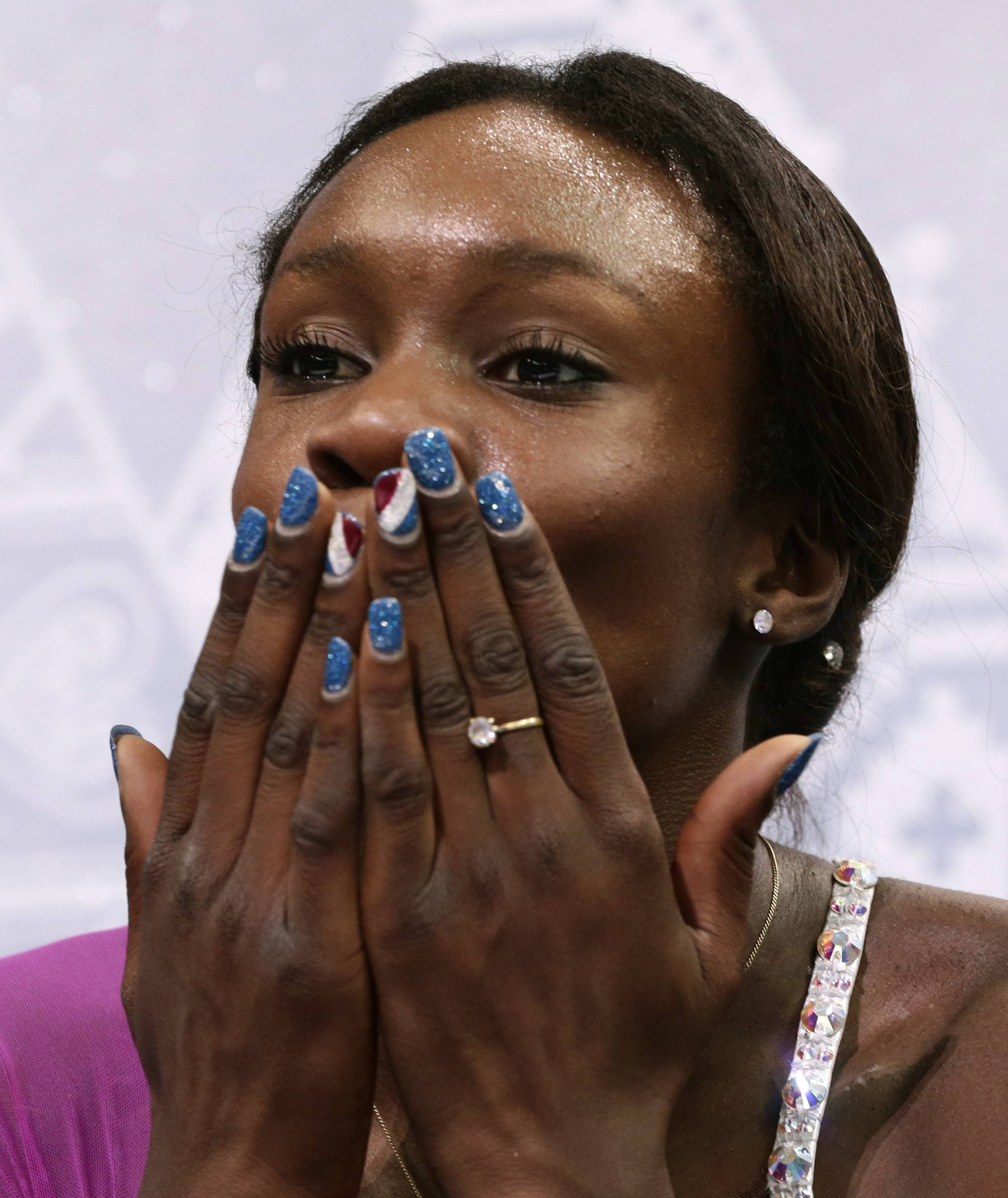 Mae Berenice Meite of France blows a kiss to spectators as she waits in the results area after completing her routine in the women's short program figure skating competition.