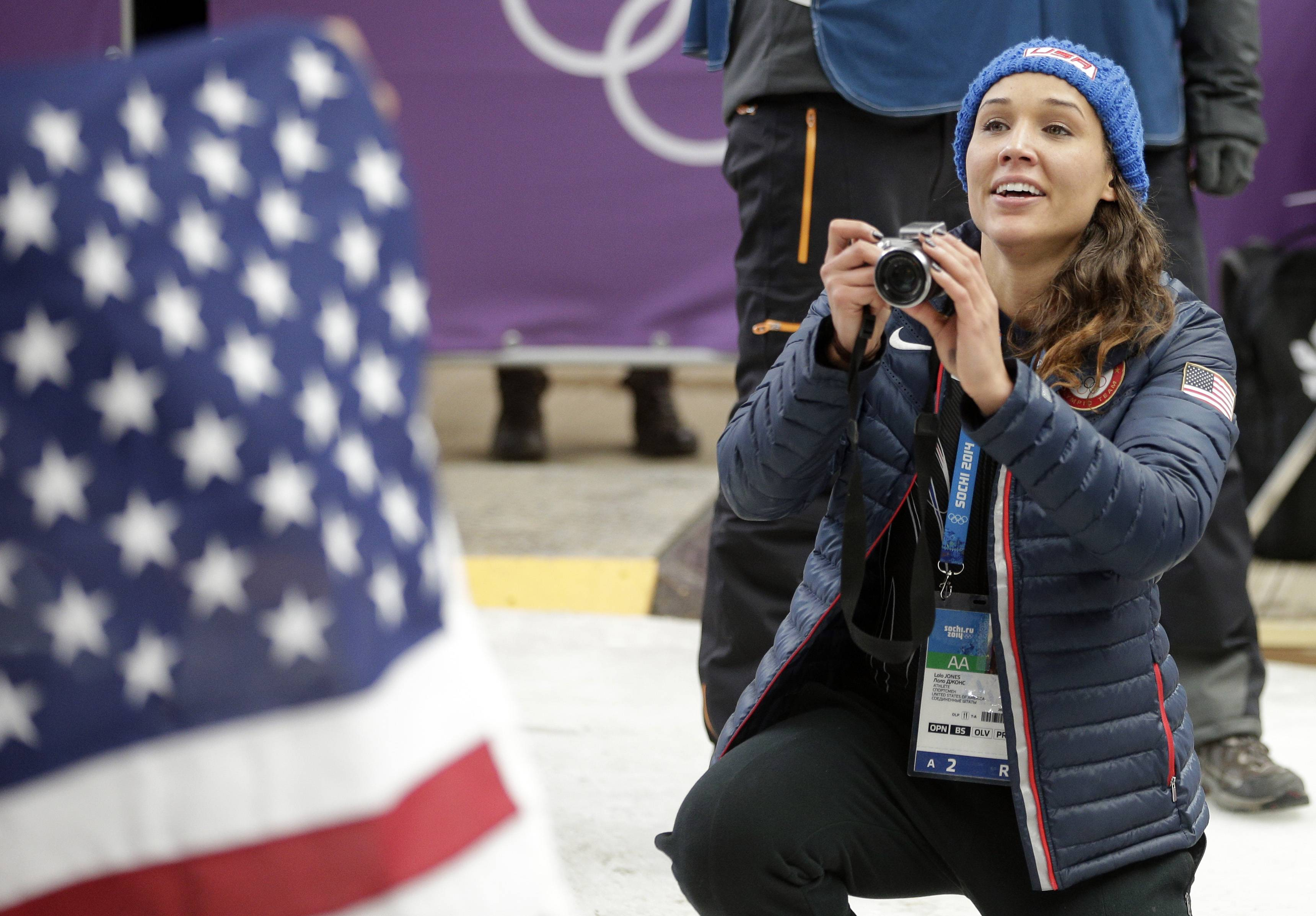 American bobsledder Lolo Jones takes pictures of her teammates after they won silver and bronze during the women's bobsled competition.