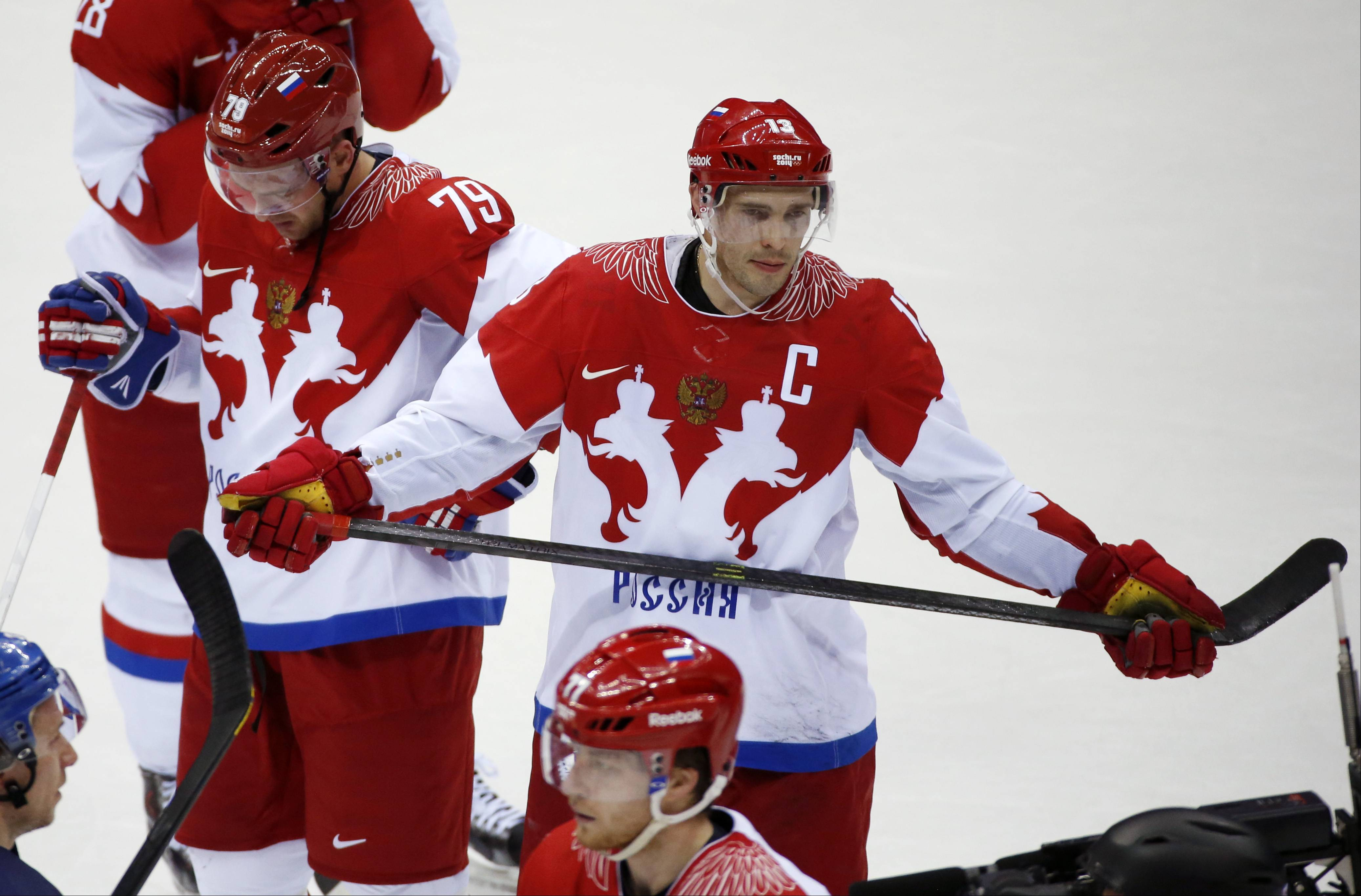 Russia defenseman Andrei Markov, left, and forward Pavel Datsyuk react after Russia lost 3-1 to Finland in a men's quarterfinal ice hockey game at the 2014 Winter Olympics Wednesday.