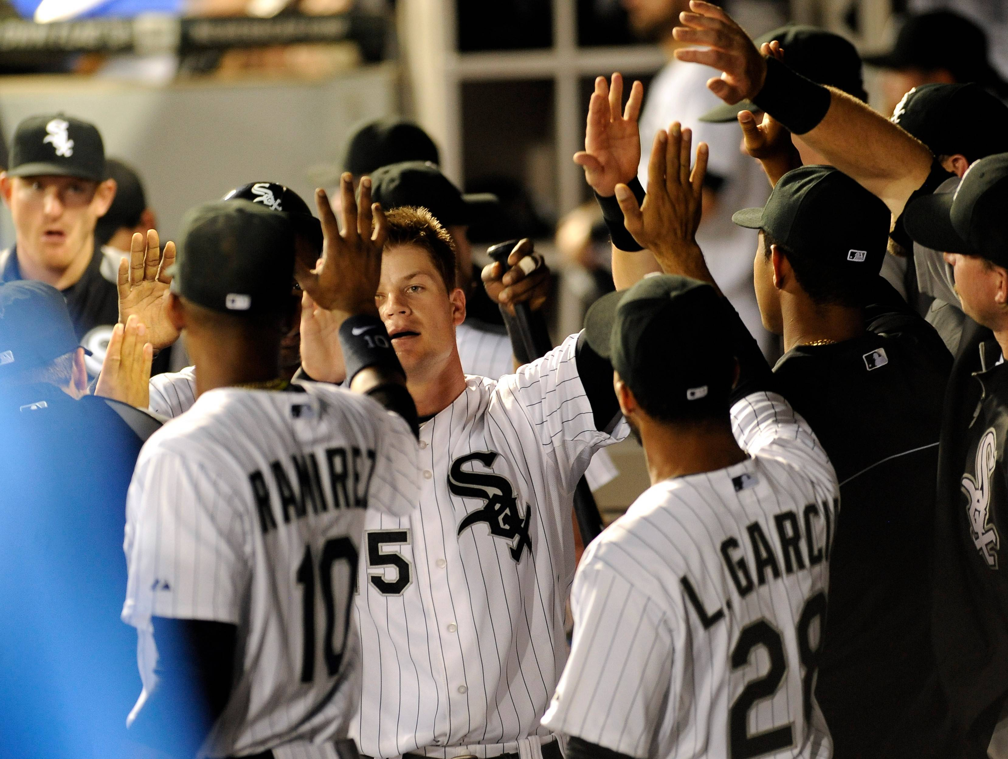 Gordan Beckham celebrates in the White Sox' dugout after scoring a run in a game against the Tigers late last season.