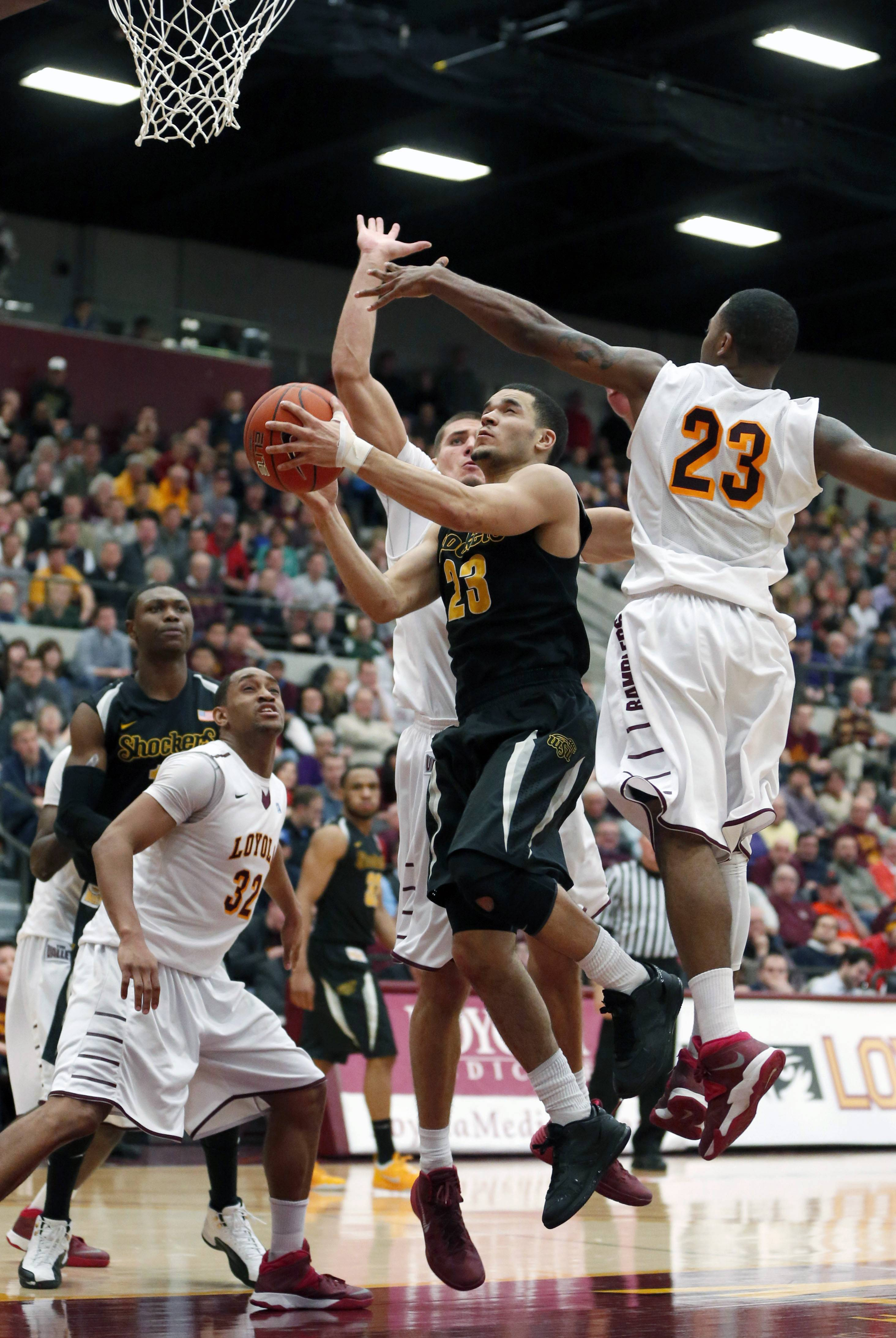 Wichita State guard Fred VanVleet (23) scores between Loyola of Chicago guard Christian Thomas (32) Nick Osborne, behind and Jeff White during the second half of an NCAA college basketball game Wednesday, Feb. 19, 2014, in Chicago. Wichita State won 88-74.