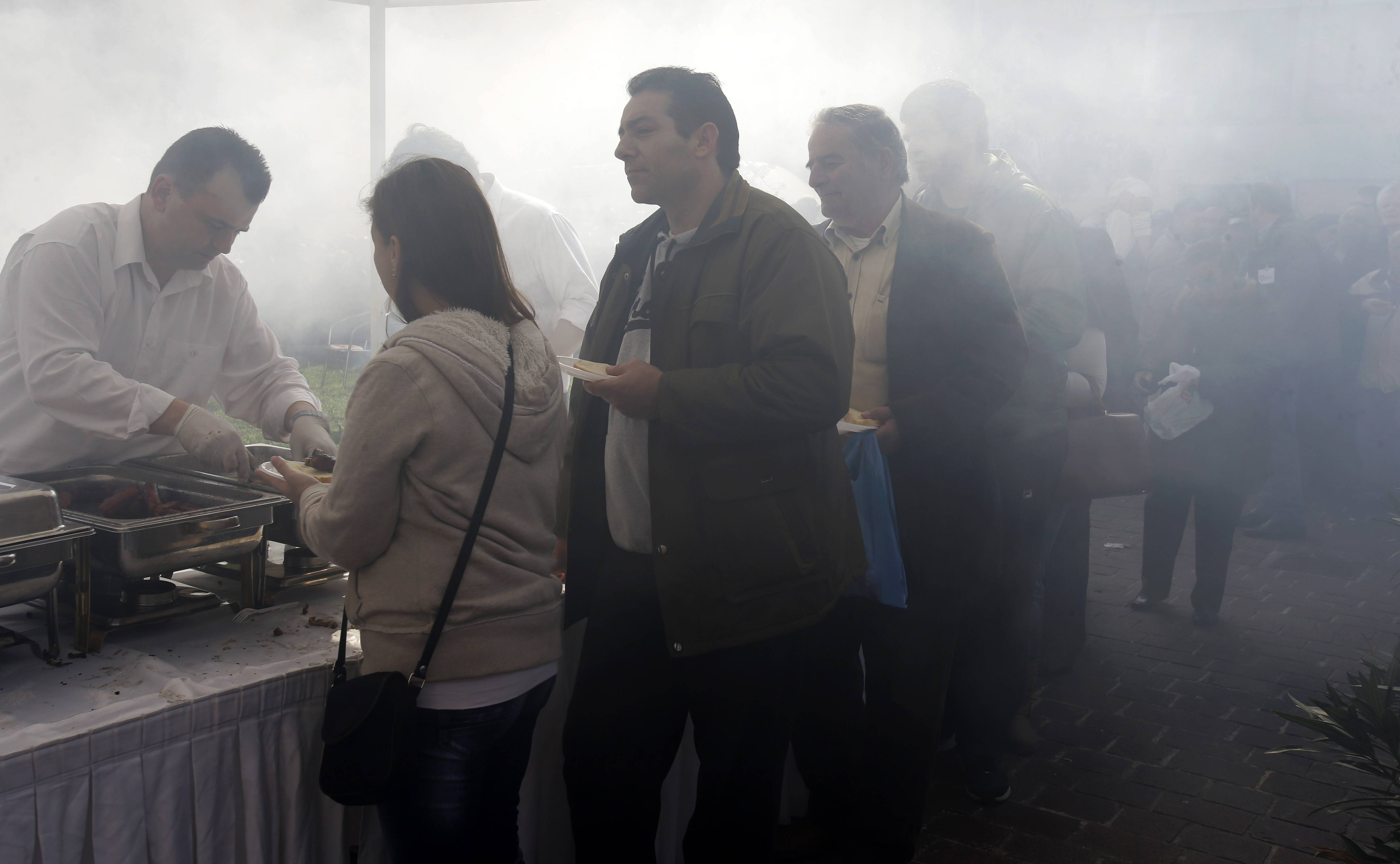 "Hundreds of Athenians queue for free meat at the Athens central meat market amid clouds of smoke from grills Thursday. The handouts were organized by meat market traders, as part of the annual celebrations for ""Barbecue Thursday"" _ a raucous pre-Easter celebration for meat lovers. But amid Greece's acute recession and unemployment, the prospect of free meat has come to attract ever-larger crowds."