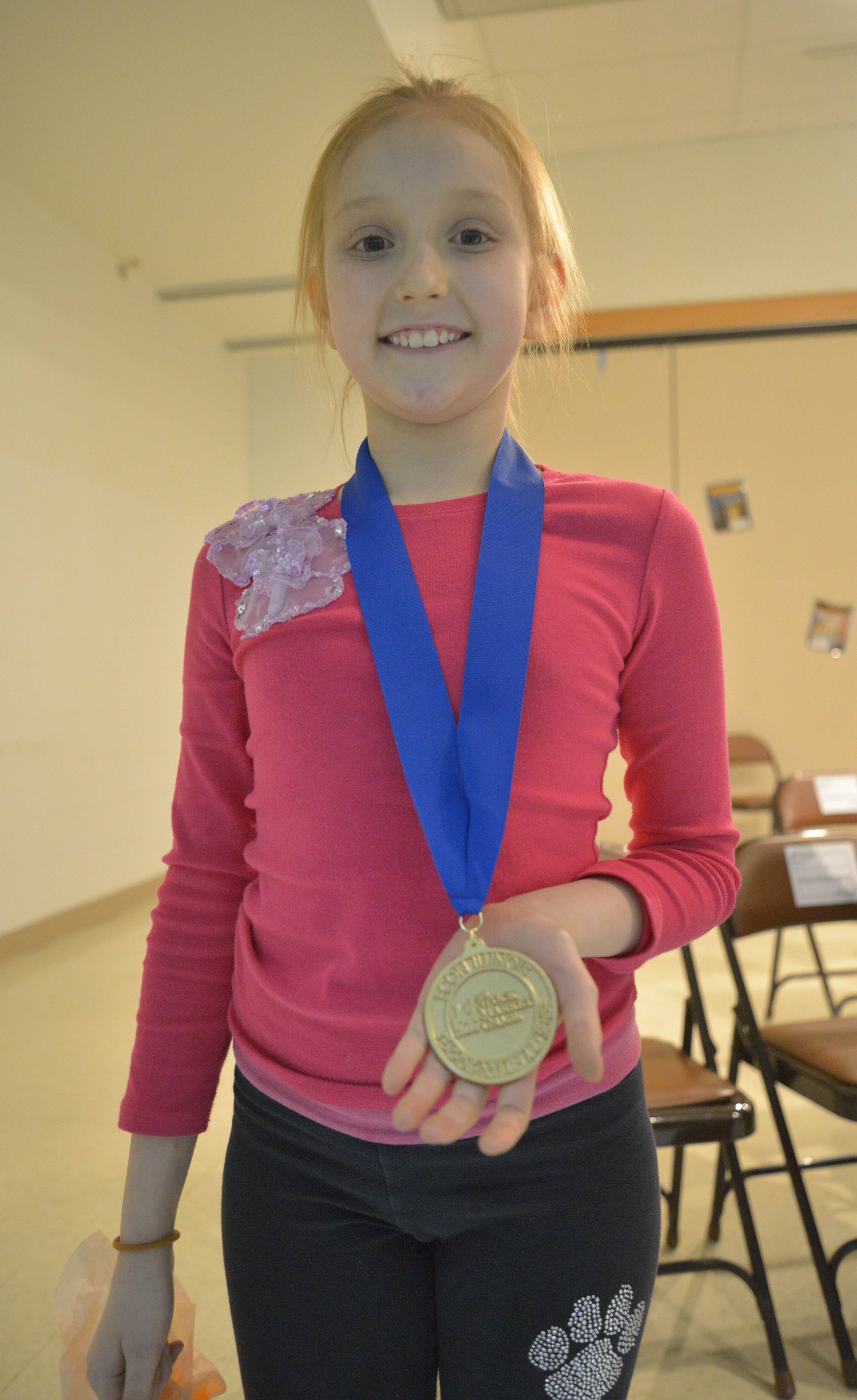 Katherine Smirnov, 10, displays the medal she received Thursday for winning the elementary division of the fall 2013 InvestWrite essay contest for her piece recommending Boeing and Microsoft as sound long-term investments. Katherine attends Naperville's Fry Elementary School in Indian Prairie Unit District 204 and wrote the essay as part of a class taught by Sharon Phares.