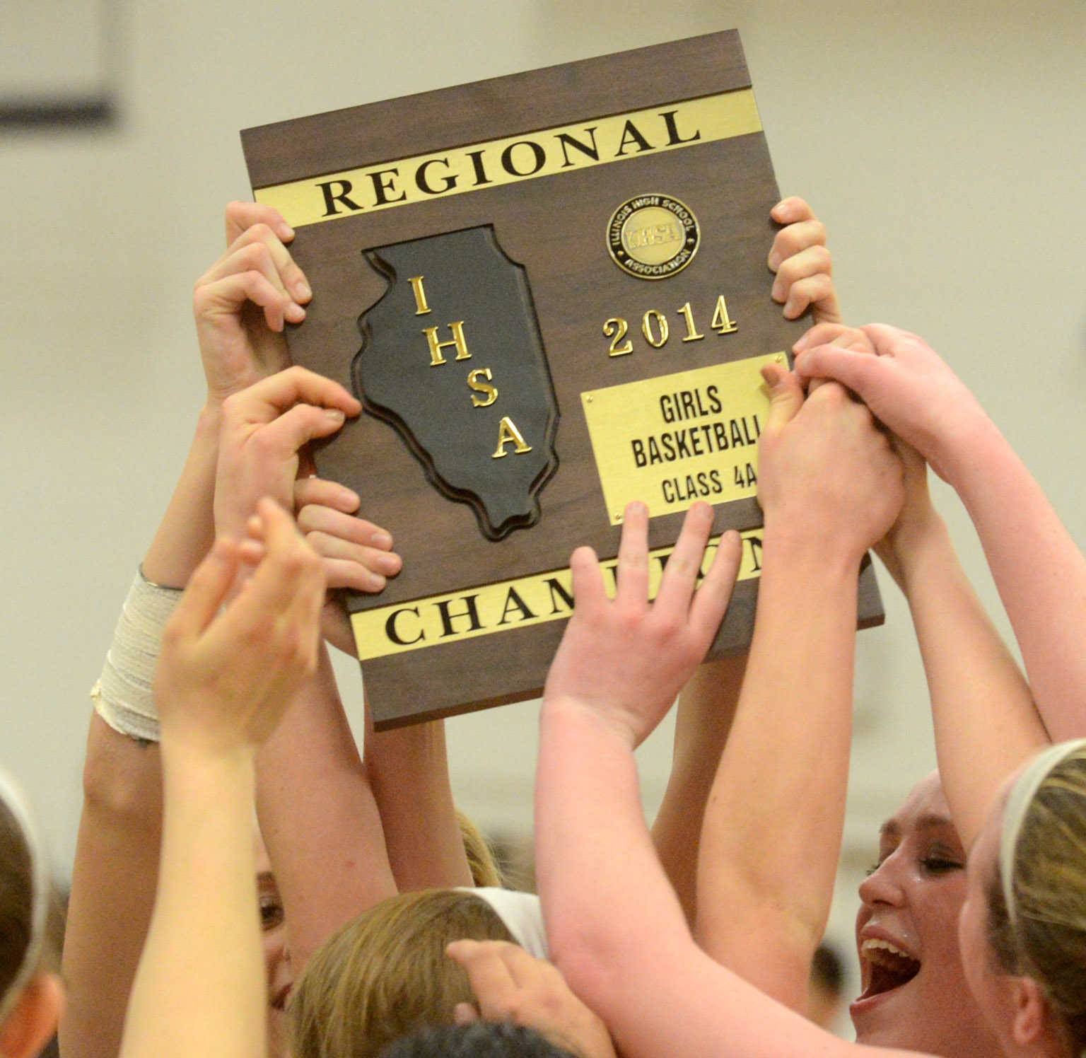 Players from South Elgin's Storm hoist their hardware after the IHSA Class 4A Jacobs regional championship girls basketball game at Algonquin on Monday night.