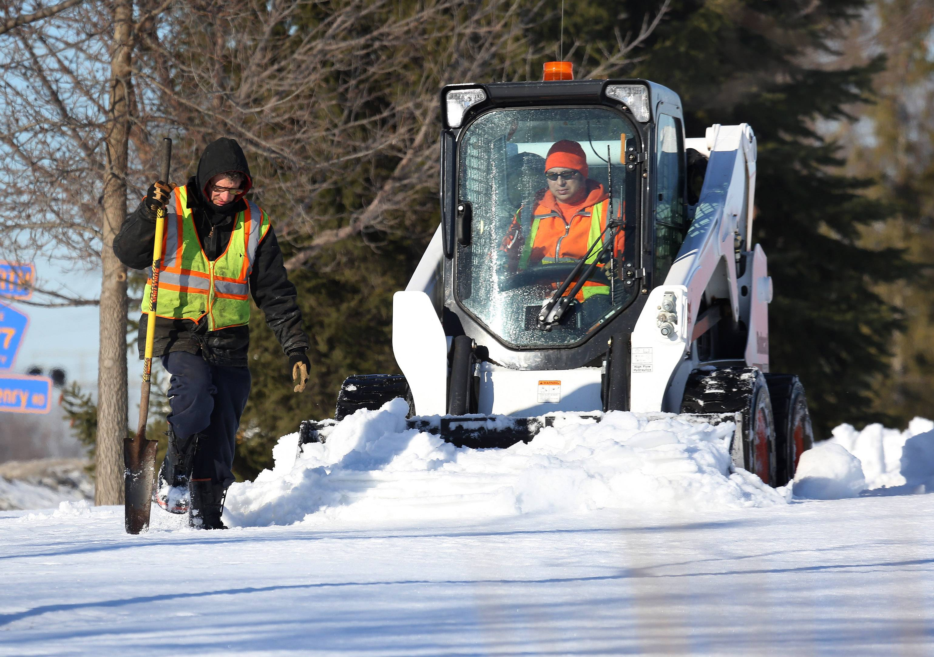 Hawthorn Woods public works employees Rick Stevens, left, and Rich Richter operate a front-end loader to clear trails at Community Park. The Winter Wonderland carnival is on Saturday.