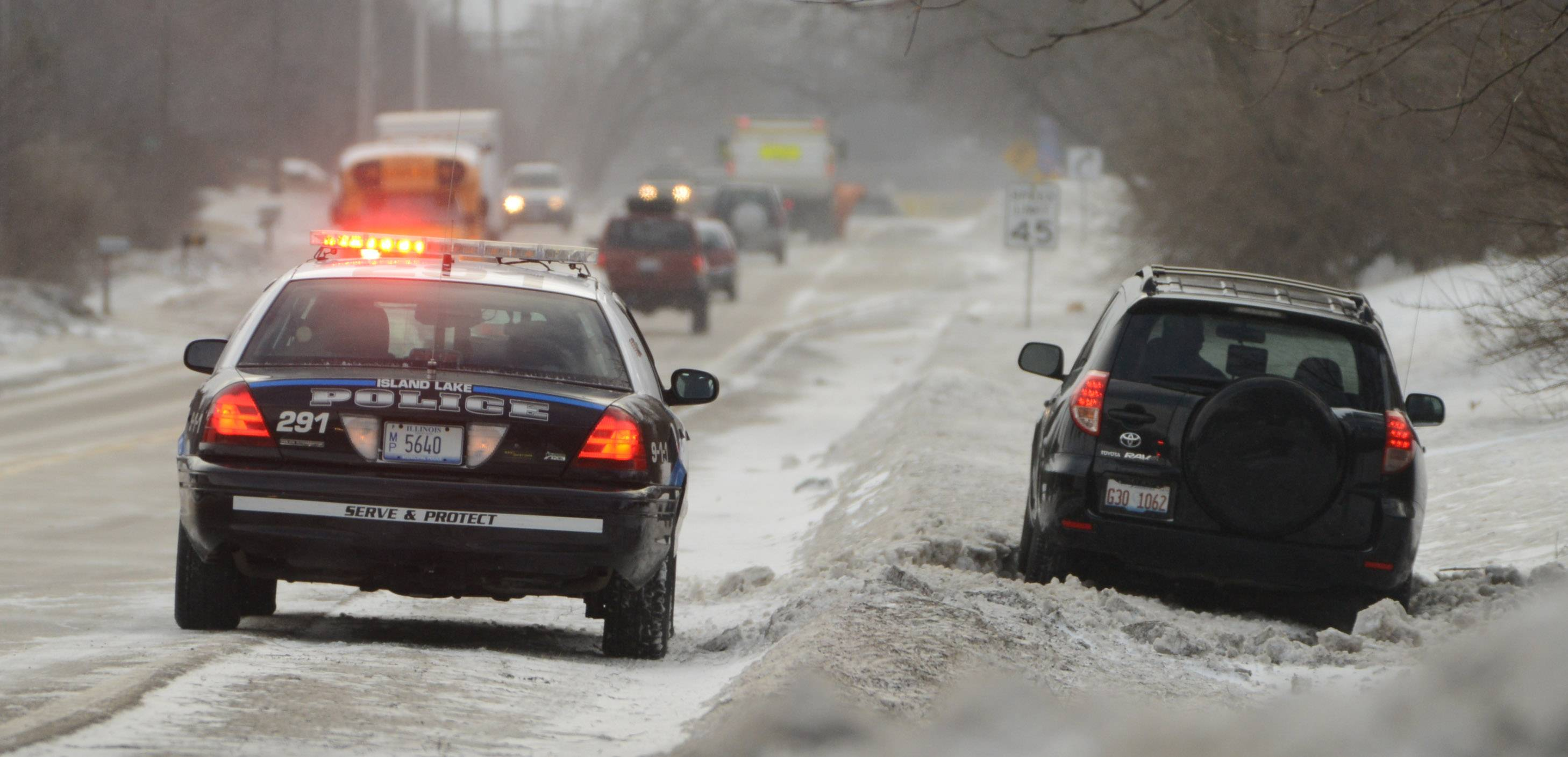 An Island Lake police officer stands by after a driver slides into a ditch along Route 176 Friday morning. Colder and windy weather moved in Friday morning leaving many roads icy.