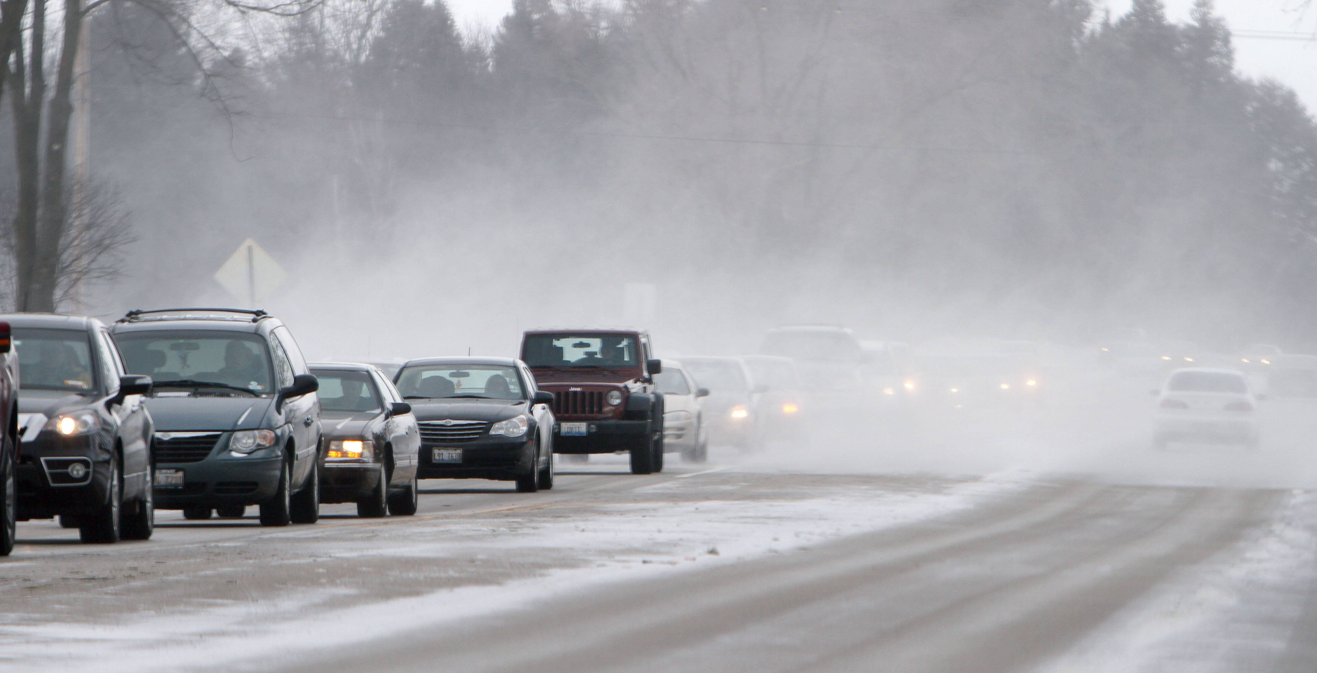 High winds are causing blowing and drifting snow along Butterfield Road in Libertyville Friday.