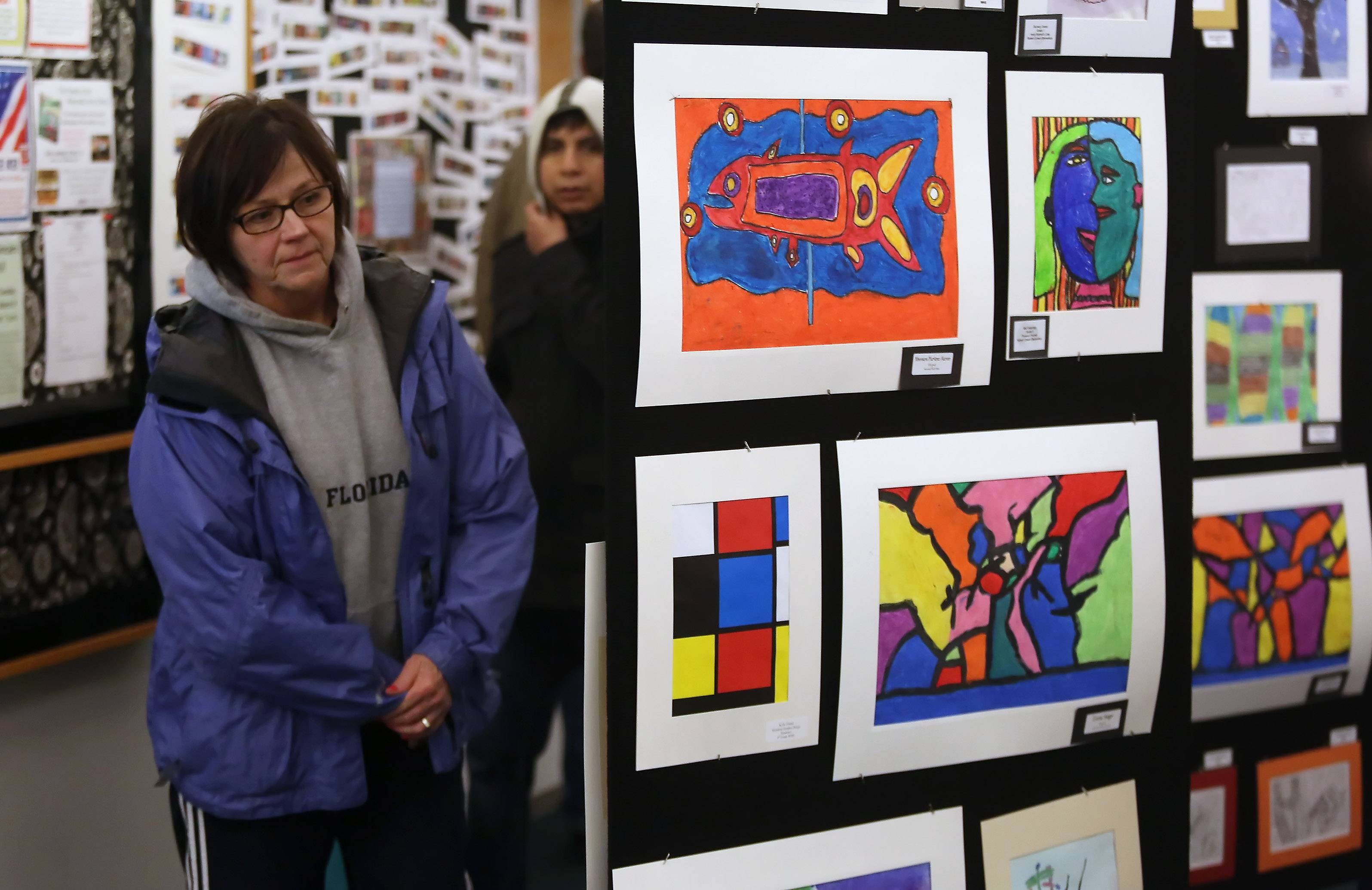 Grandmother Cheryl Thiel looks for fourth-grader Belle Johnson's artwork during the Studio 118 open house Thursday at Wauconda Area Library. The show featured more than 600 pieces of art by District 118 students.