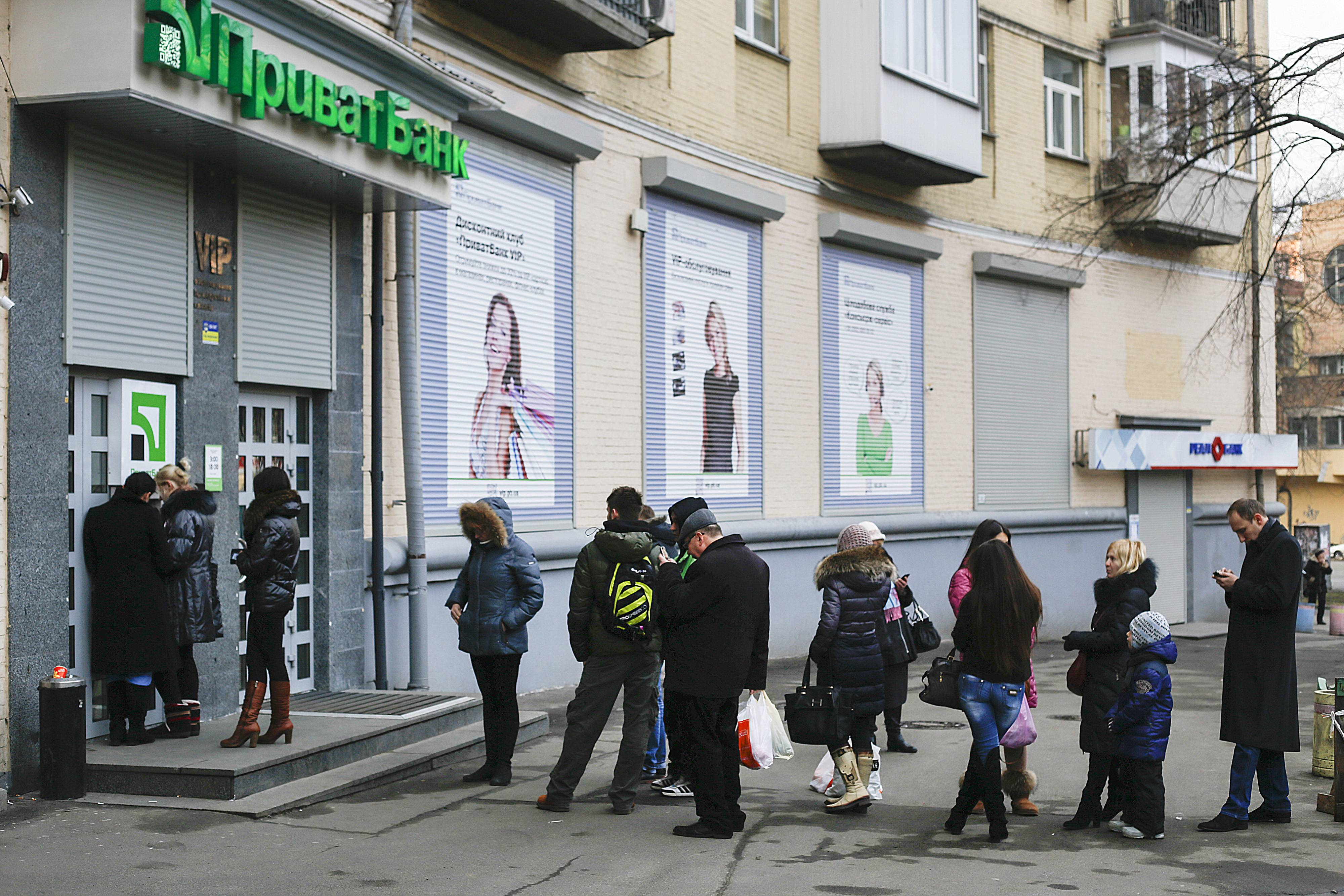 Customers queue to withdraw currency from an automated teller machine in Kiev, Ukraine, Thursday. Western nations, including the U.S., are considering sanctions against the Ukraine government.