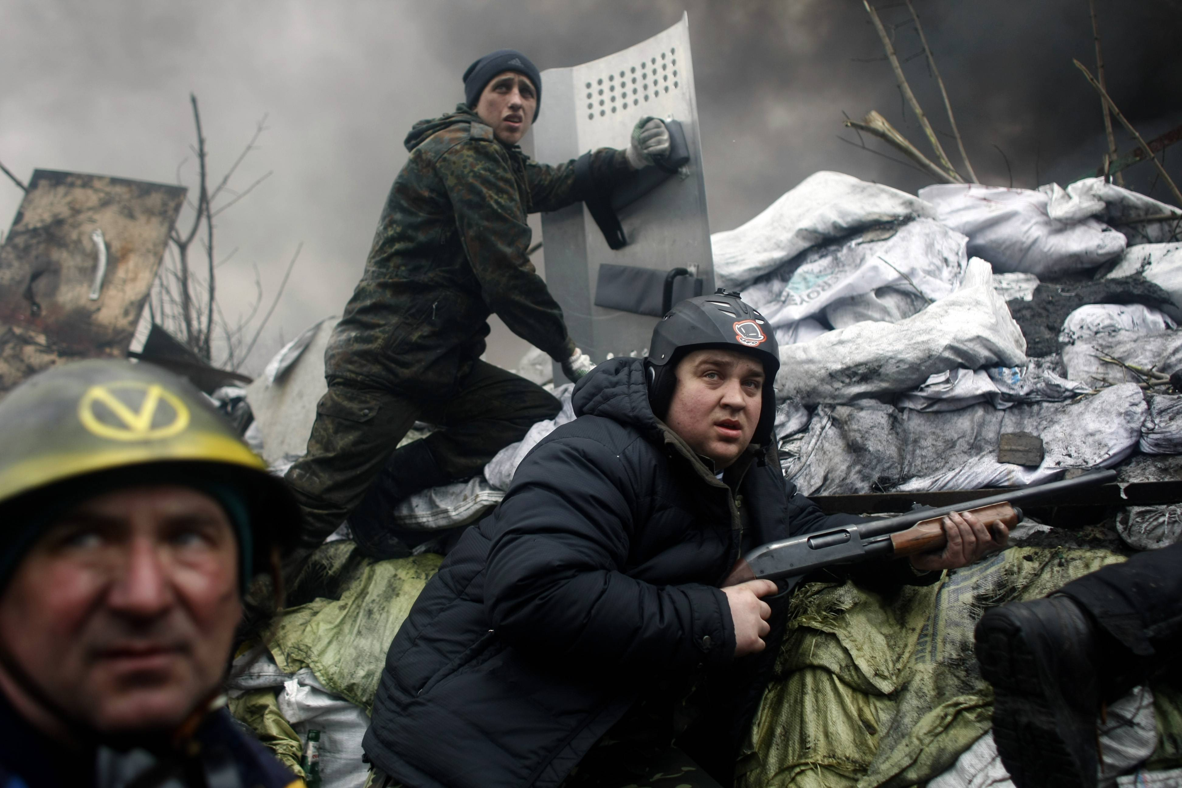 An anti-government protester holds a firearm as he mans a barricade on the outskirts of Independence Square in Kiev, Ukraine, Thursday, Feb. 20, 2014. Fierce clashes between police and protesters, some including gunfire, shattered a brief truce in Ukraine's besieged capital Thursday, killing numerous people. The deaths came in a new eruption of violence just hours after the country's embattled president and the opposition leaders demanding his resignation called for a truce and negotiations to try to resolve Ukraine's political crisis.