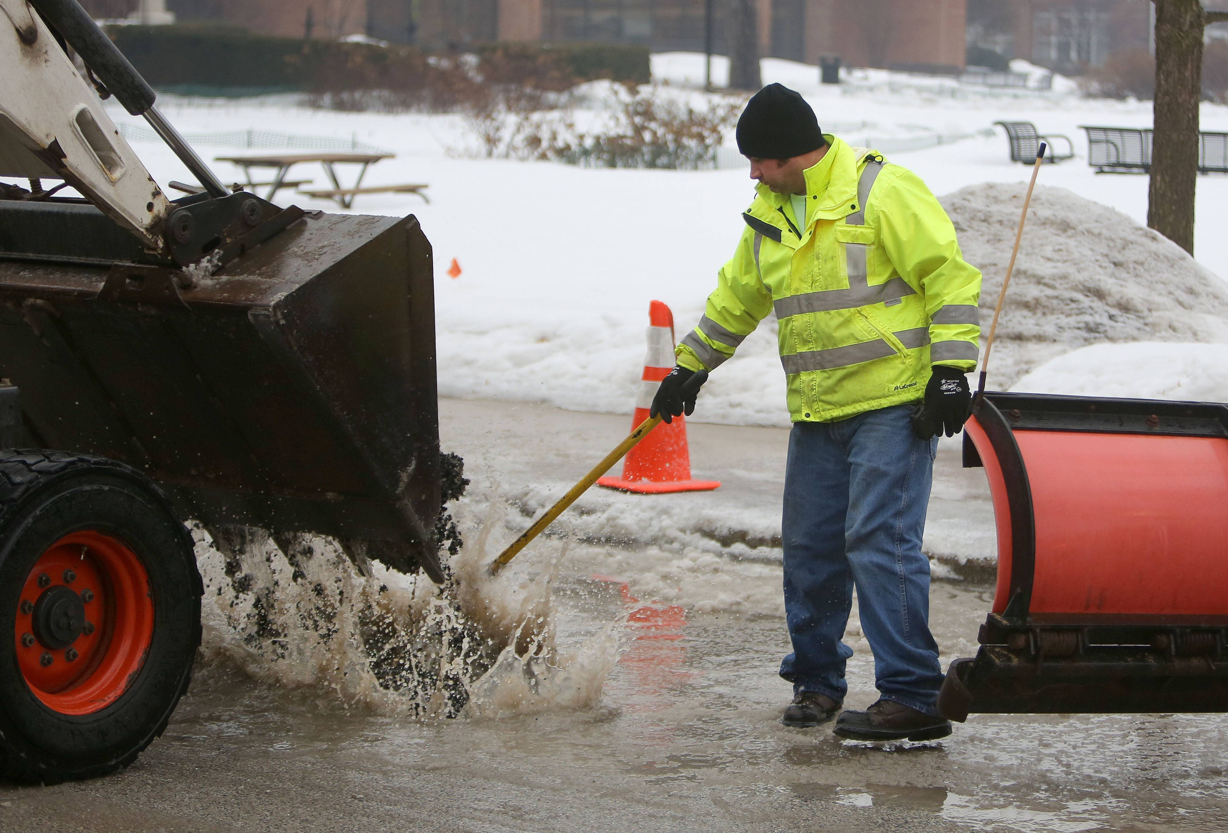 Libertyville Public Works employee Daryl Sellek fills in a huge pothole that's filled with water in downtown Libertyville Thursday morning.