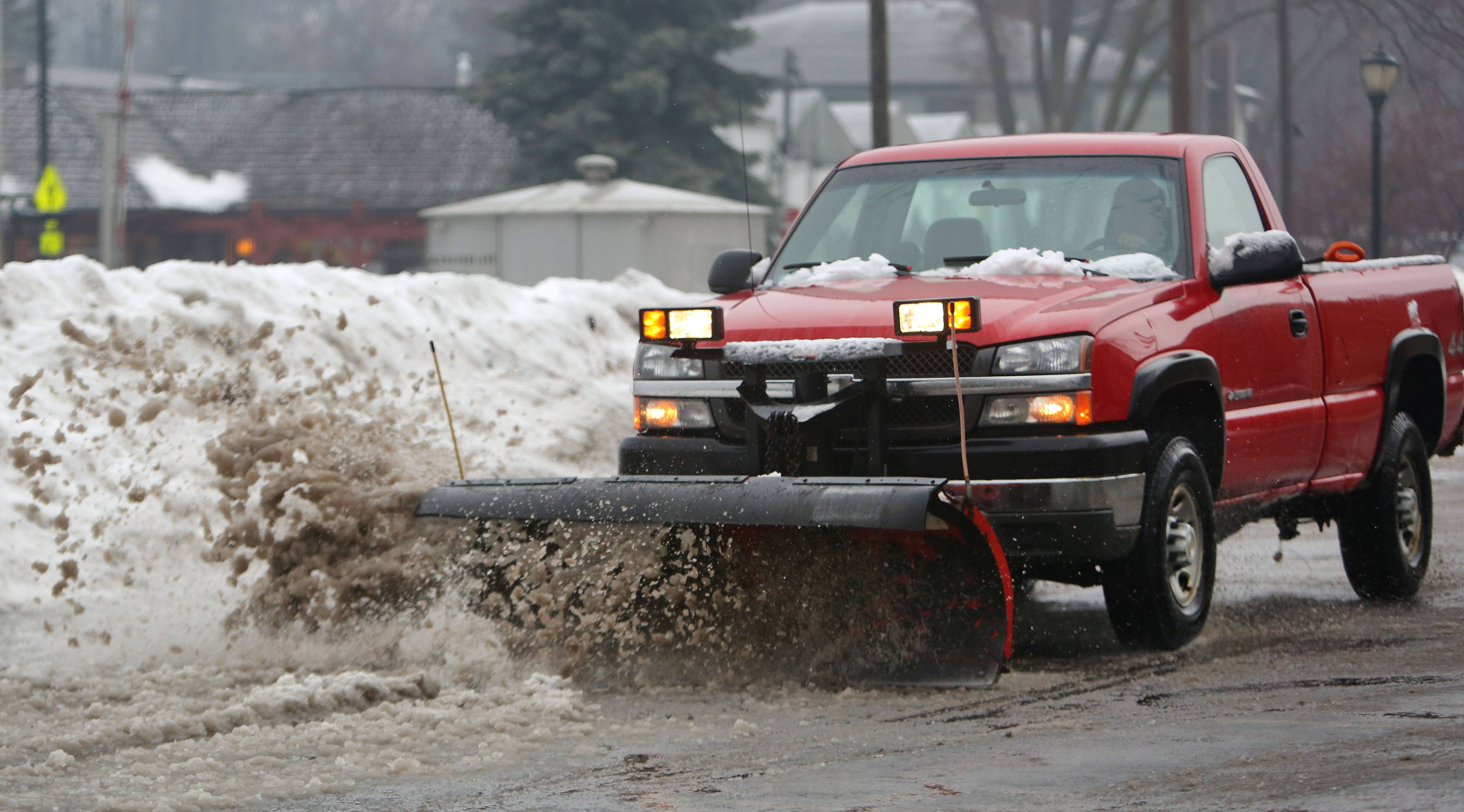 A snowplow clears slush out of a parking lot in Libertyville after a winter storm covered the area with freezing rain Thursday morning.