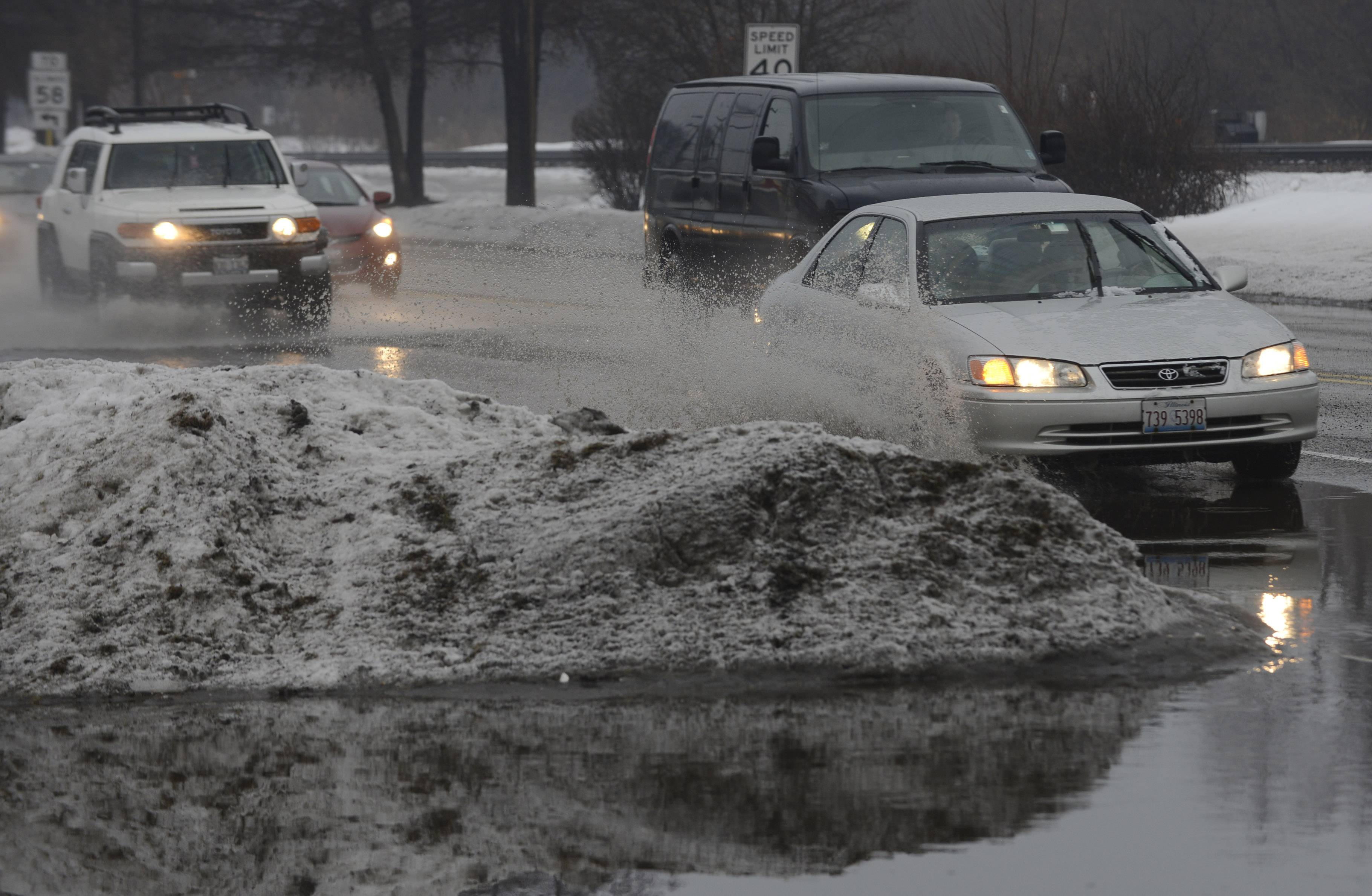 Cars navigate a large puddle caused by rain and melting snow along Northwest Highway near the Lattof YMCA in Des Plaines Thursday morning.