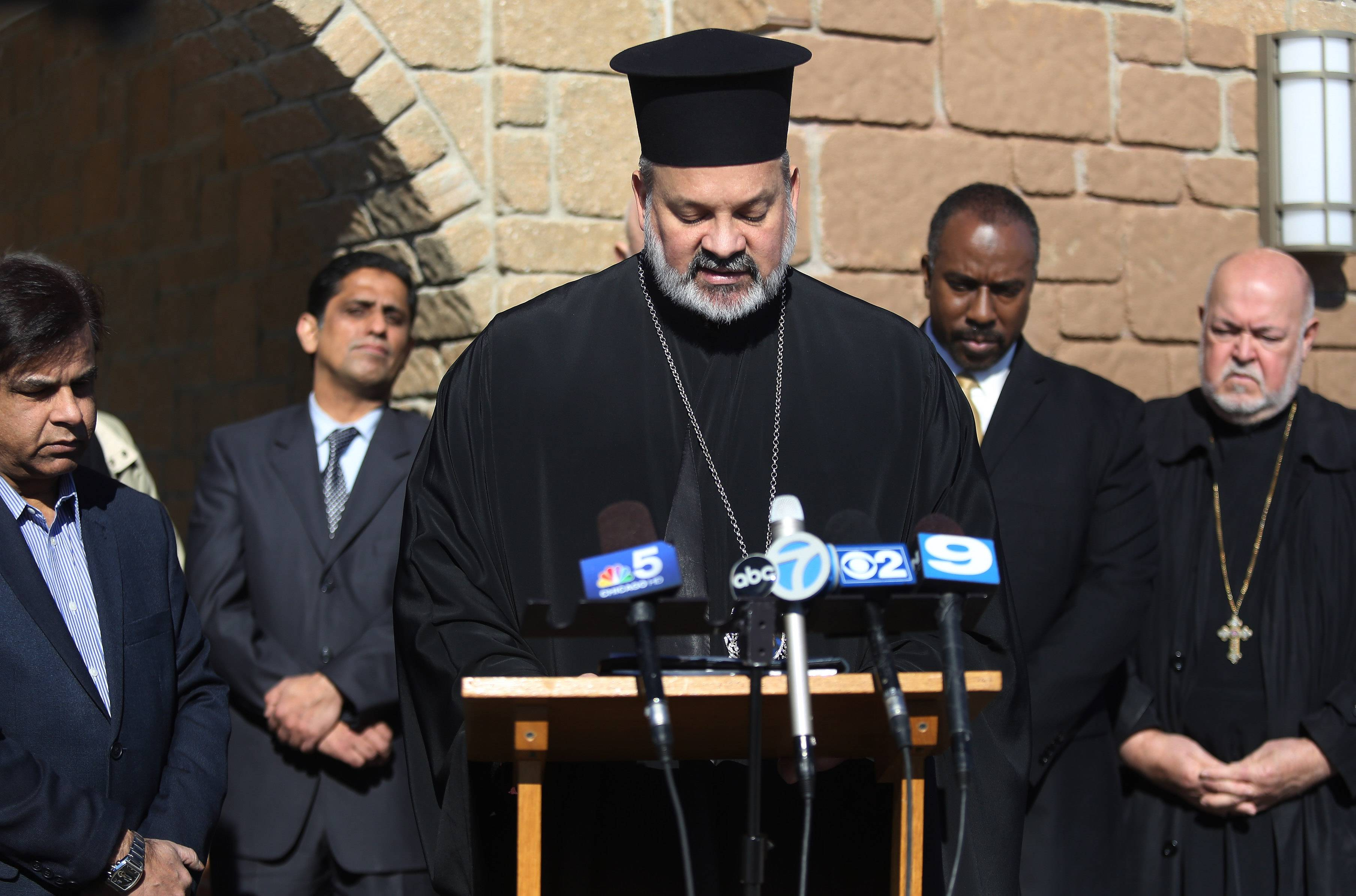 Bishop Demetrios of the Metropolis of Chicago says a prayer at St. Demetrios Greek Orthodox Church in Waukegan as he is joined by leaders of other faiths during a news conference Wednesday to discuss recent vandalism.