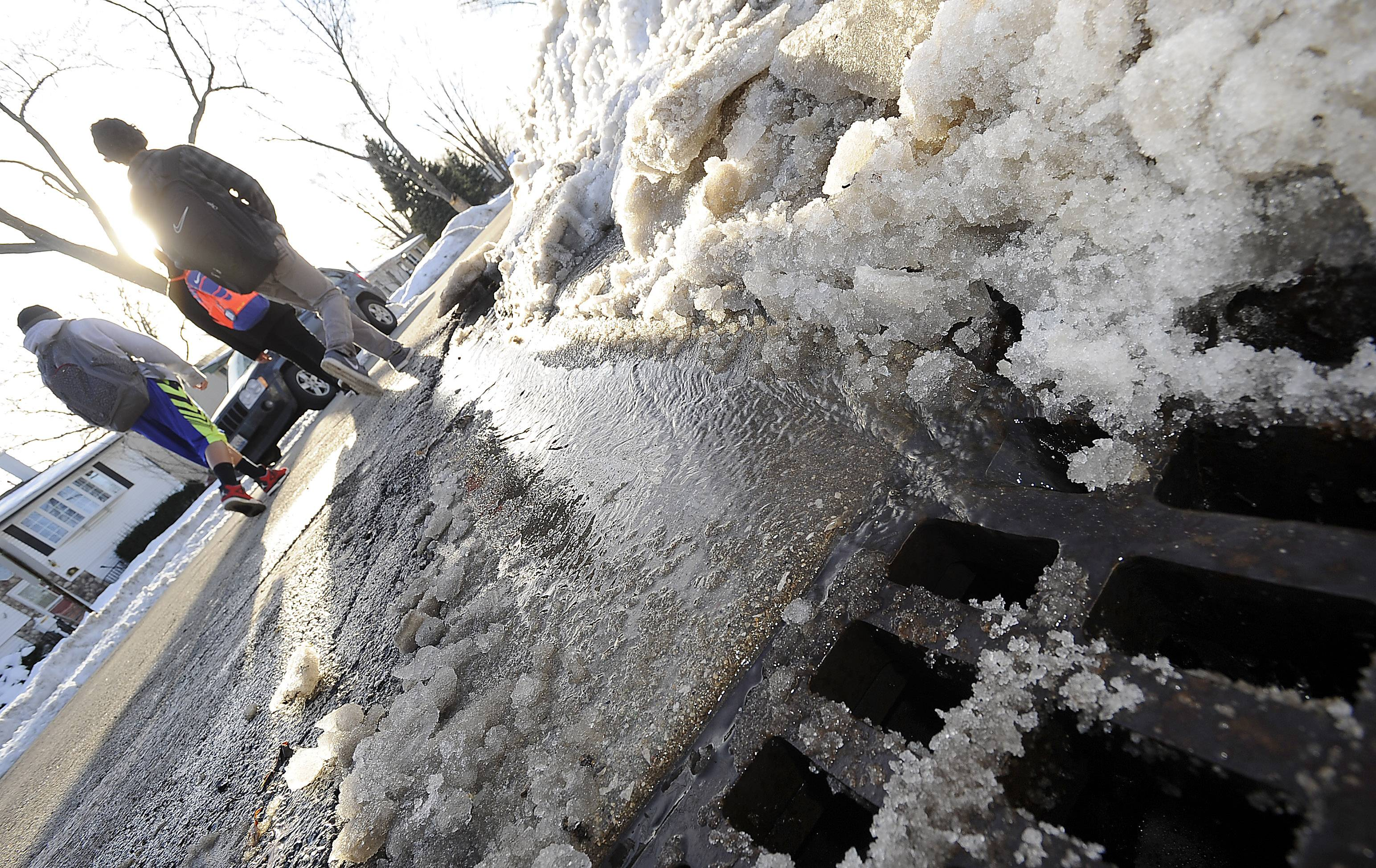 Water flows freely along a Wheeling street after public works crews cleared snow and ice away from a storm drain at the intersection of Palm and Willow.