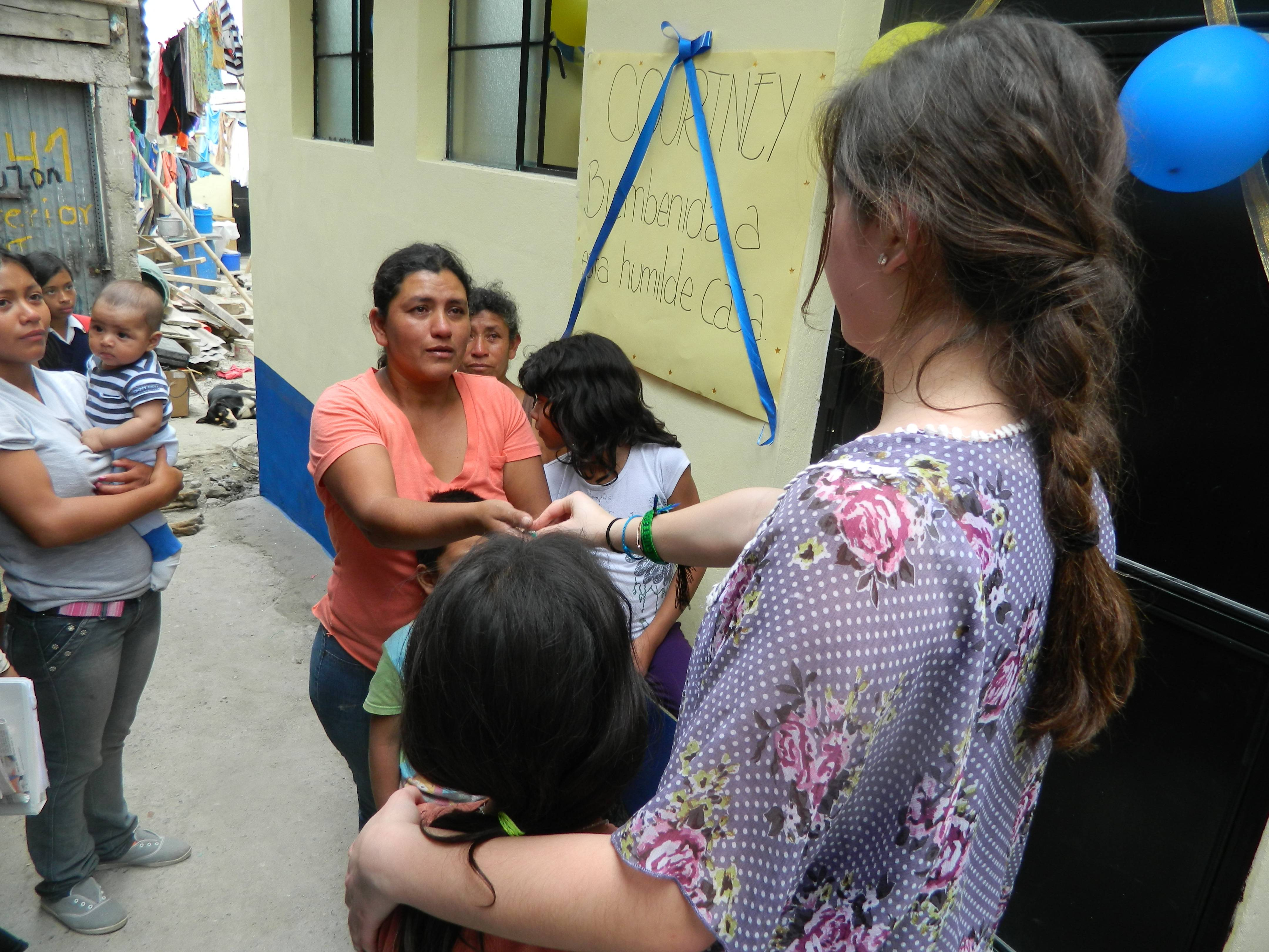 "Courtney Quigley, right, hands the keys to a new home to a family in Guatemala City. The home was built through ""Hope's in Style,"" a fundraiser in Barrington organized by Courtney and her twin sister, Ashley."
