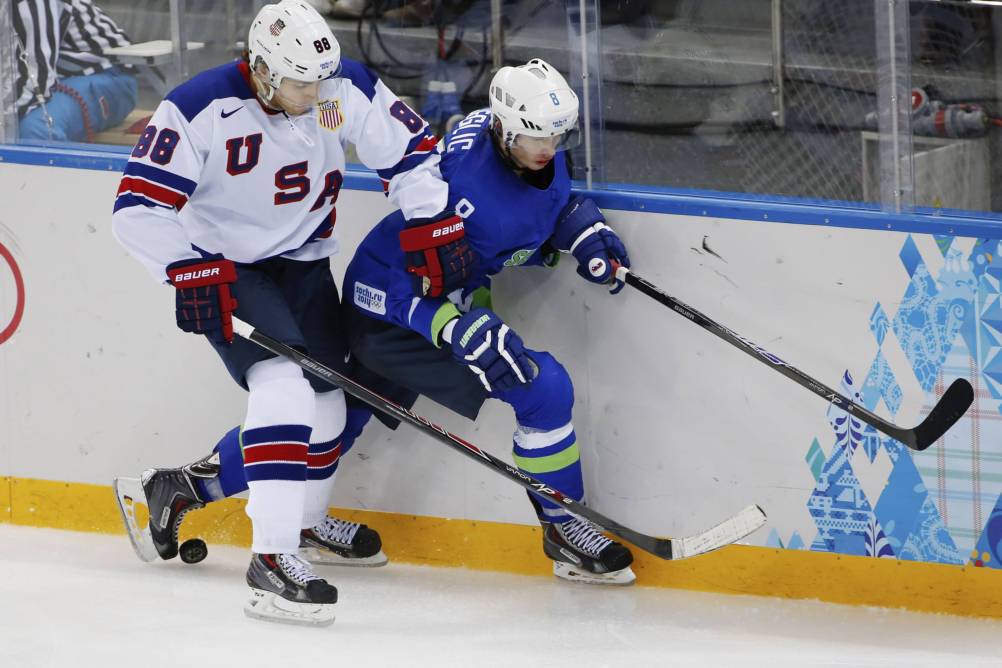 USA forward Patrick Kane pins Slovenia forward Ziga Jeglic against the boards during the 2014 Winter Olympics men's ice hockey game at Shayba Arena Sunday, Feb. 16, 2014, in Sochi, Russia.