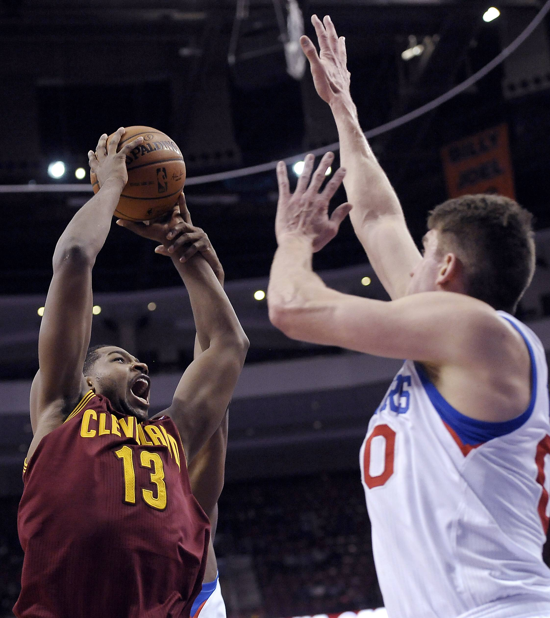 Cleveland's Tristan Thompson (13) takes a shot over Philadelphia's' Spencer Hawes in a game on Tuesday. On Thursday, the Cavs acquired Hawes.