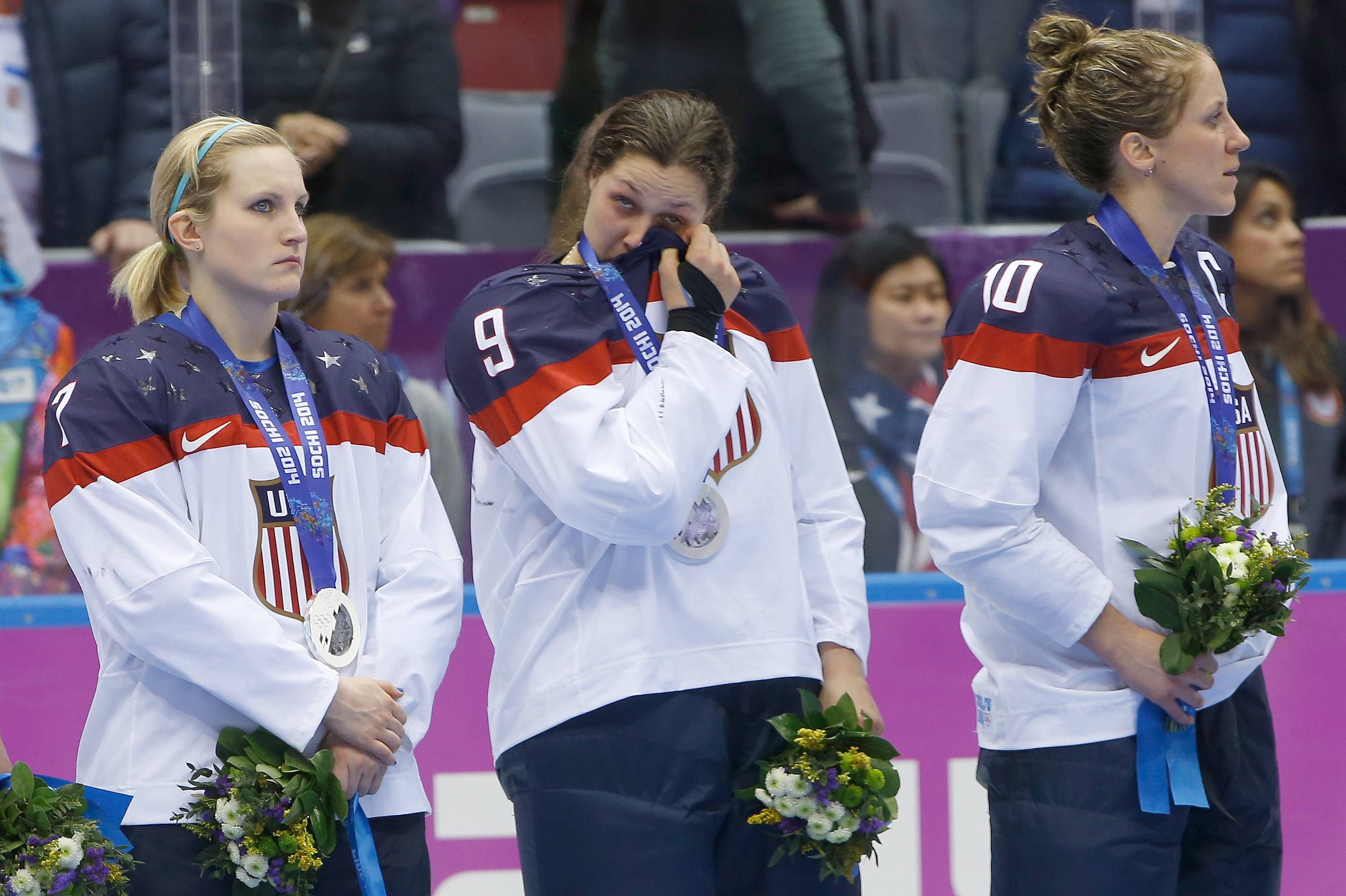 Megan Bozek of the United States (9) wipes a tear as she stand with Monique Lamoureux of the United States (7),  and Meghan Duggan of the United States (10) during the medal ceremony for women's ice hockey.