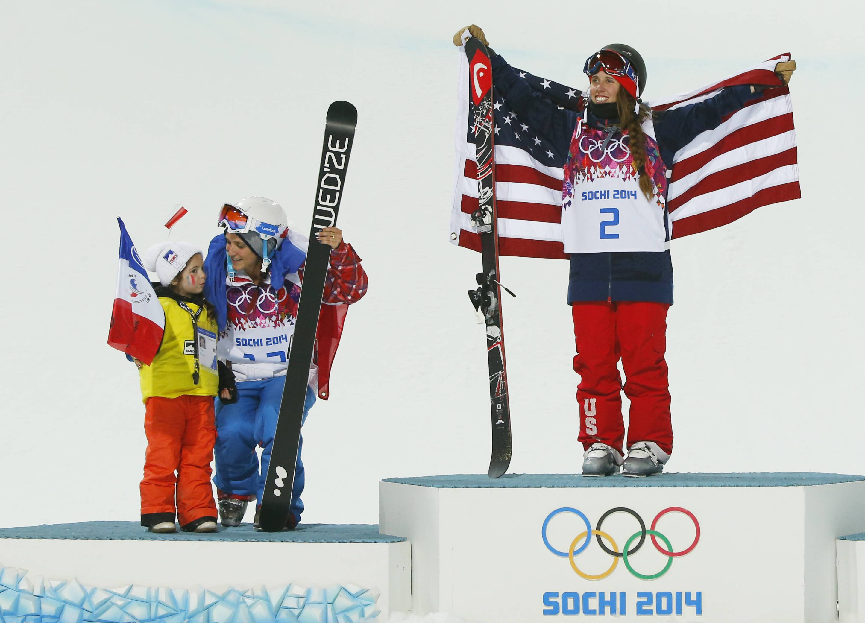 Maddie Bowman of the United States, right, celebrates after winning the gold medal in the women's ski halfpipe final, with silver medalist Marie Martinod of France, left, and Martinod's daughter Meli Rose.