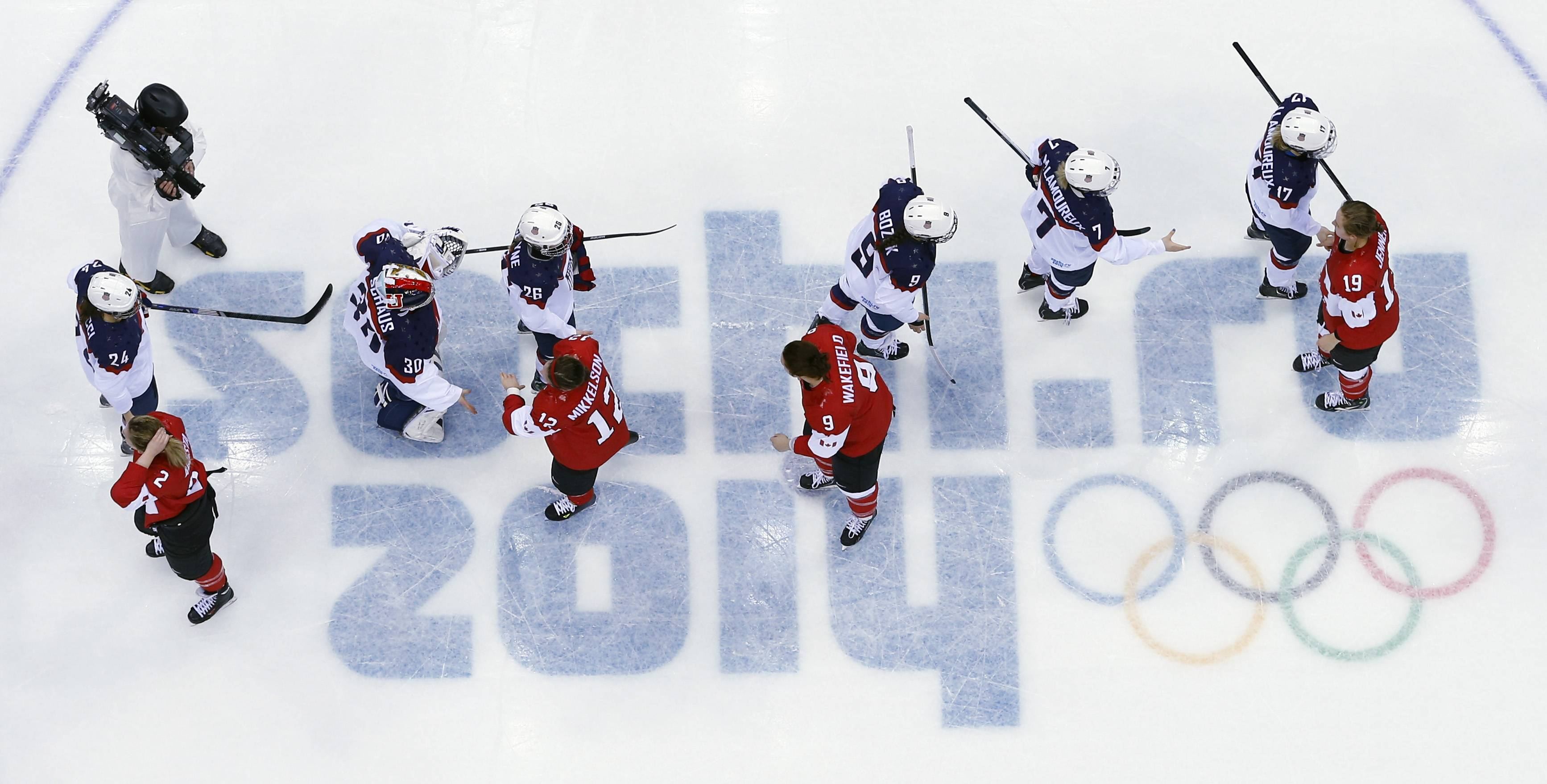 USA and Canada players shake hands after the women's gold medal ice hockey game.