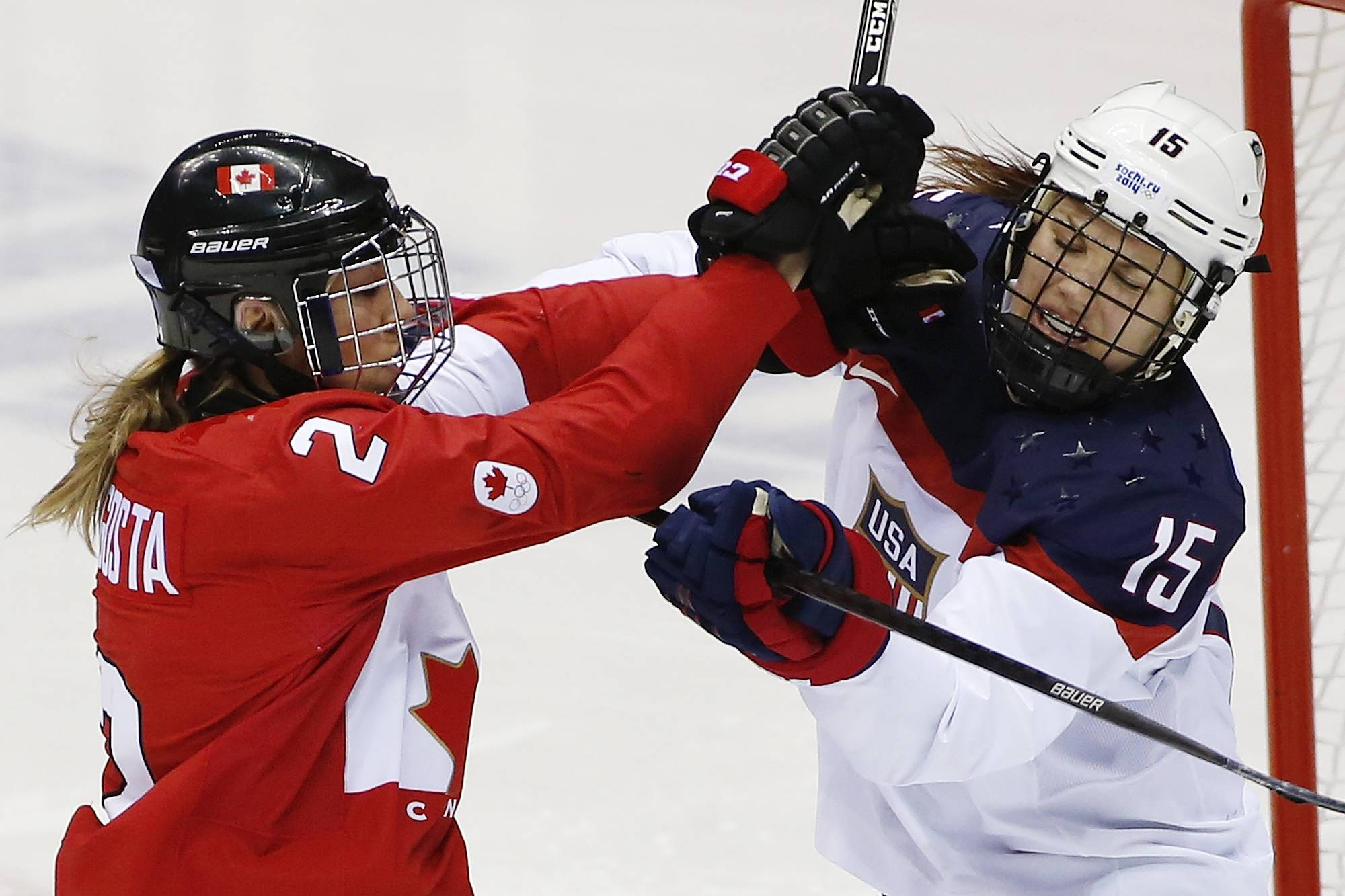 Meghan Agosta-Marciano of Canada (2) and Anne Schleper of the United States (15) mix it up during the second period of the women's gold medal ice hockey game.
