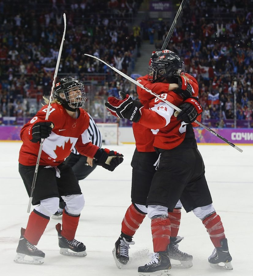 Haley Irwin of Canada (21) celebrates Thursday with teammates Marie-Philip Poulin (29) and Meghan Agosta-Marciano (2) after Poulin scored the tying goal against the USA during the third period of the women's gold medal ice hockey game at the 2014 Winter Olympics in Sochi, Russia.
