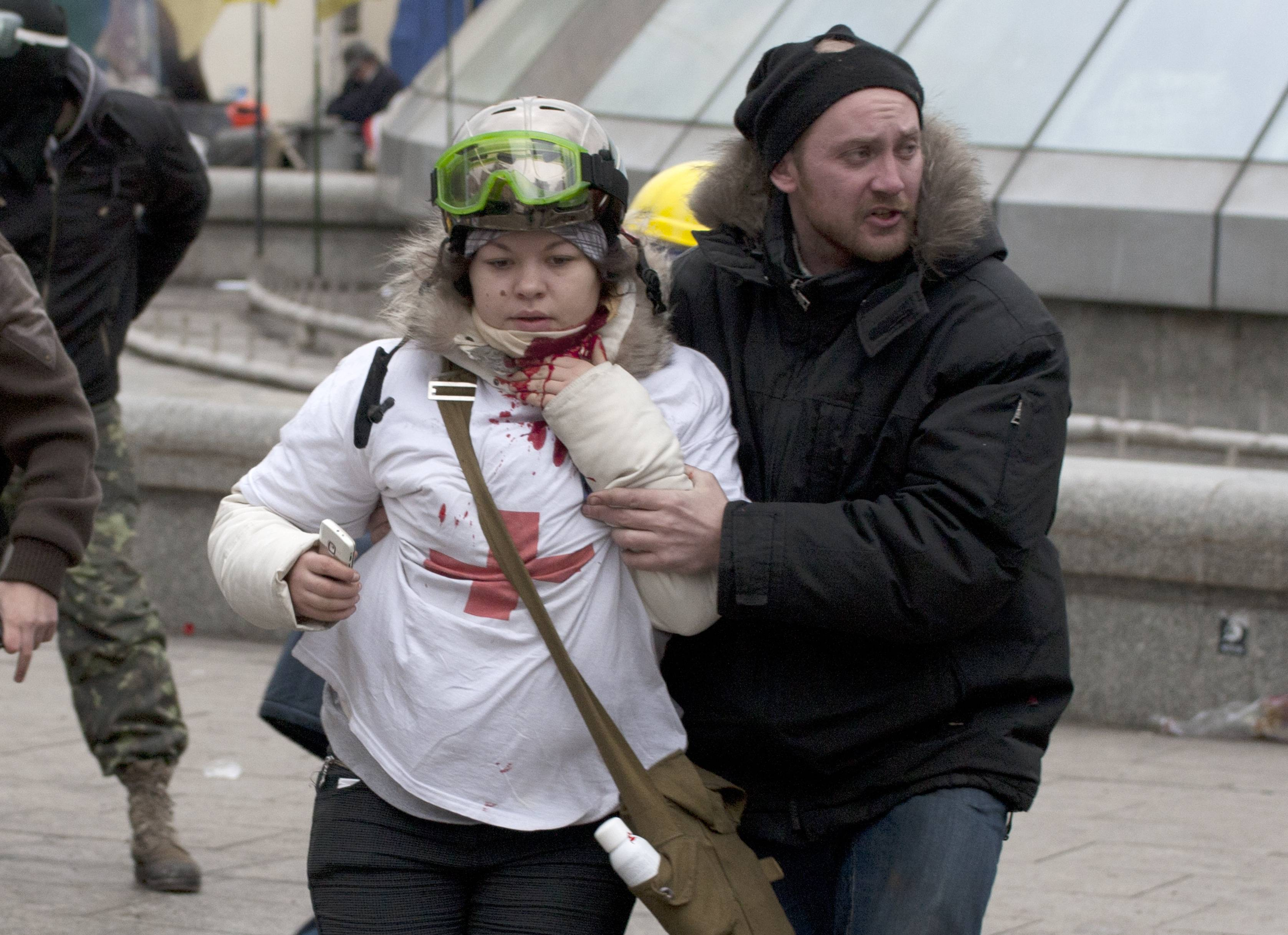 "Olesya Zhukovska, left, is helped after being shot in her neck by a sniper bullet, in Independence Square, the epicenter of the country's current unrest, Kiev, Ukraine. ""I am dying,"" Olesya Zhukovska, a 21-year-old volunteer medic, wrote on Twitter, minutes after she was shot as deadly clashes broke out in the center of the Ukrainian capital between protesters and police. The tweet, accompanied by a photo of her clutching her bleeding neck and being led away under fire, went viral, as social media users around the world presumed she had died and shared their grief and anger. But Zhukovska survived. She has become a symbol of the three-month protest of President Viktor Yanukovych's government and a movement for closer ties with the West and human rights."