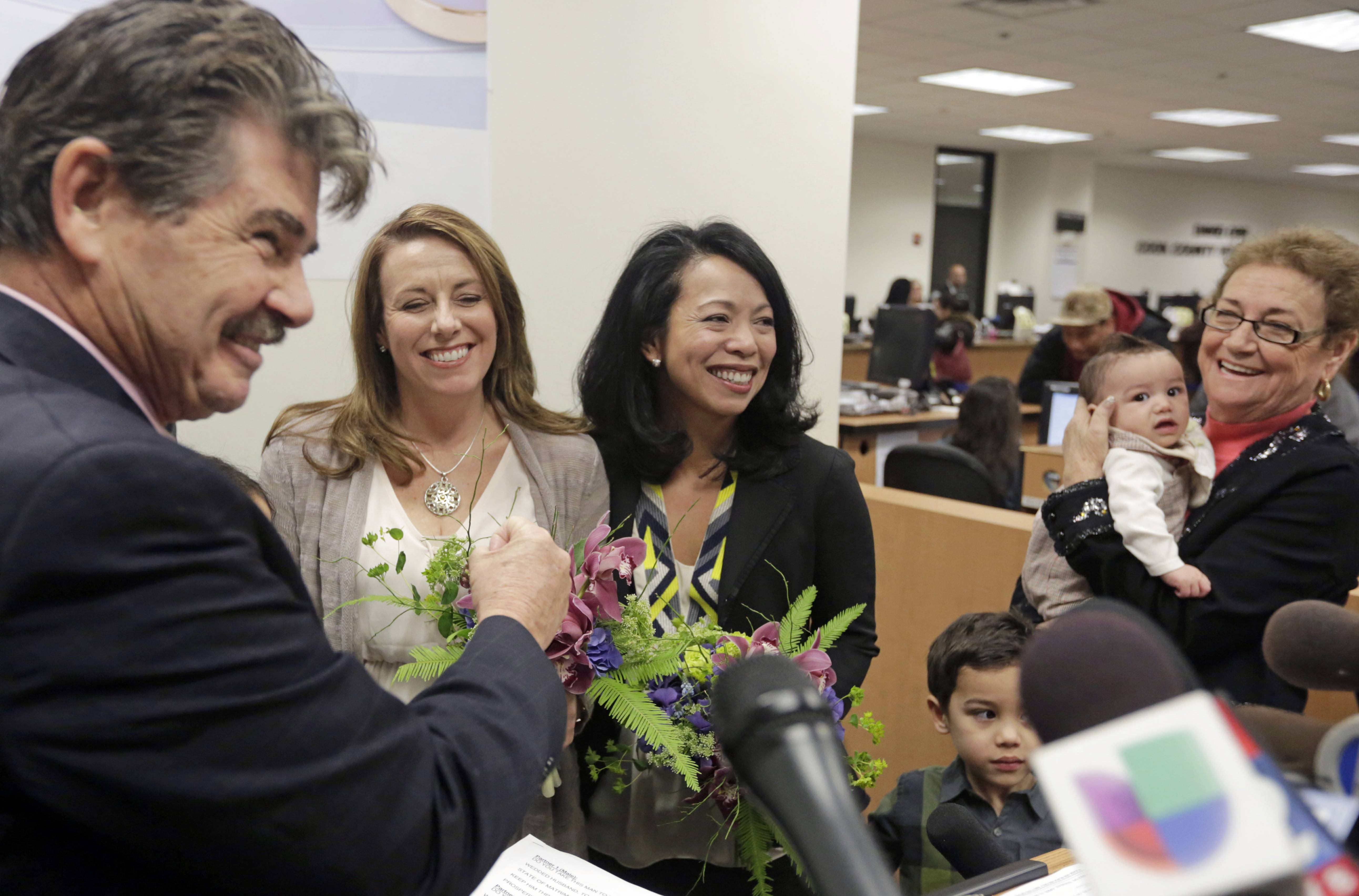 Cook County Clerk David Orr, left, performs a marriage ceremony for Theresa Volpe, second from left, and Mercedes Santos on Friday in Chicago. Same-sex couples in Illinois' Cook County began receiving marriage licenses immediately after a federal judge's ruling Friday that some attorneys could give county clerks statewide justification to also issue the documents right away.