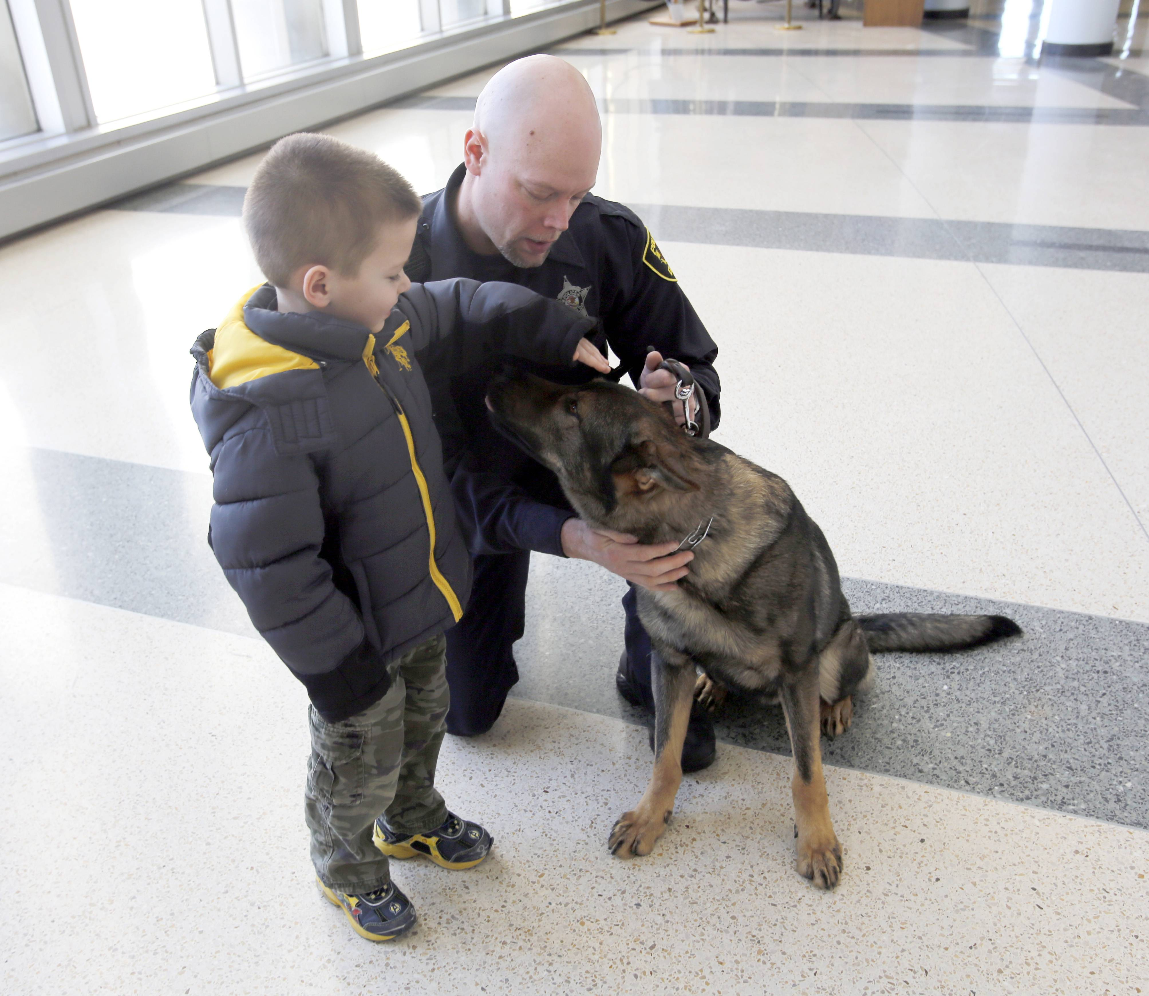 Anthony Raajcevich, 5, of Elgin, gets a chance to meet the Elgin Police Department's new police dog, Colt. Officer Chad Schuttrow is his handler.