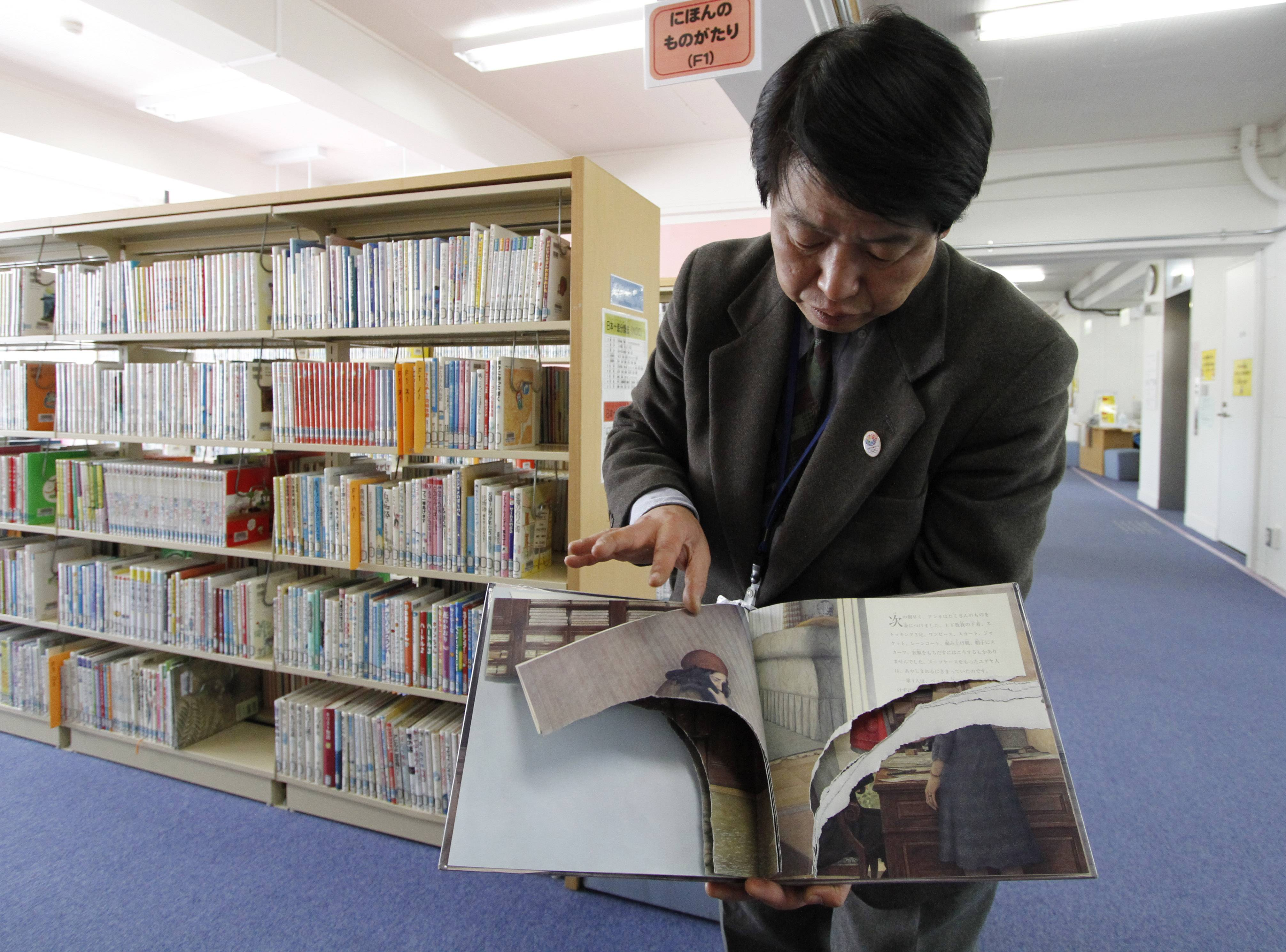 "A ripped copy of Anne Frank's ""Diary of a Young Girl"" picture book is shown by Shinjuku City Library Director Kotaro Fujimaki at the library in Tokyo Friday, Feb. 21, 2014. Tokyo Libraries said on Friday that hundreds of copies of Anne Frank's diary and related books have been found vandalized across the city's libraries in the last month, sparking fears of an anti-Semitic motive."