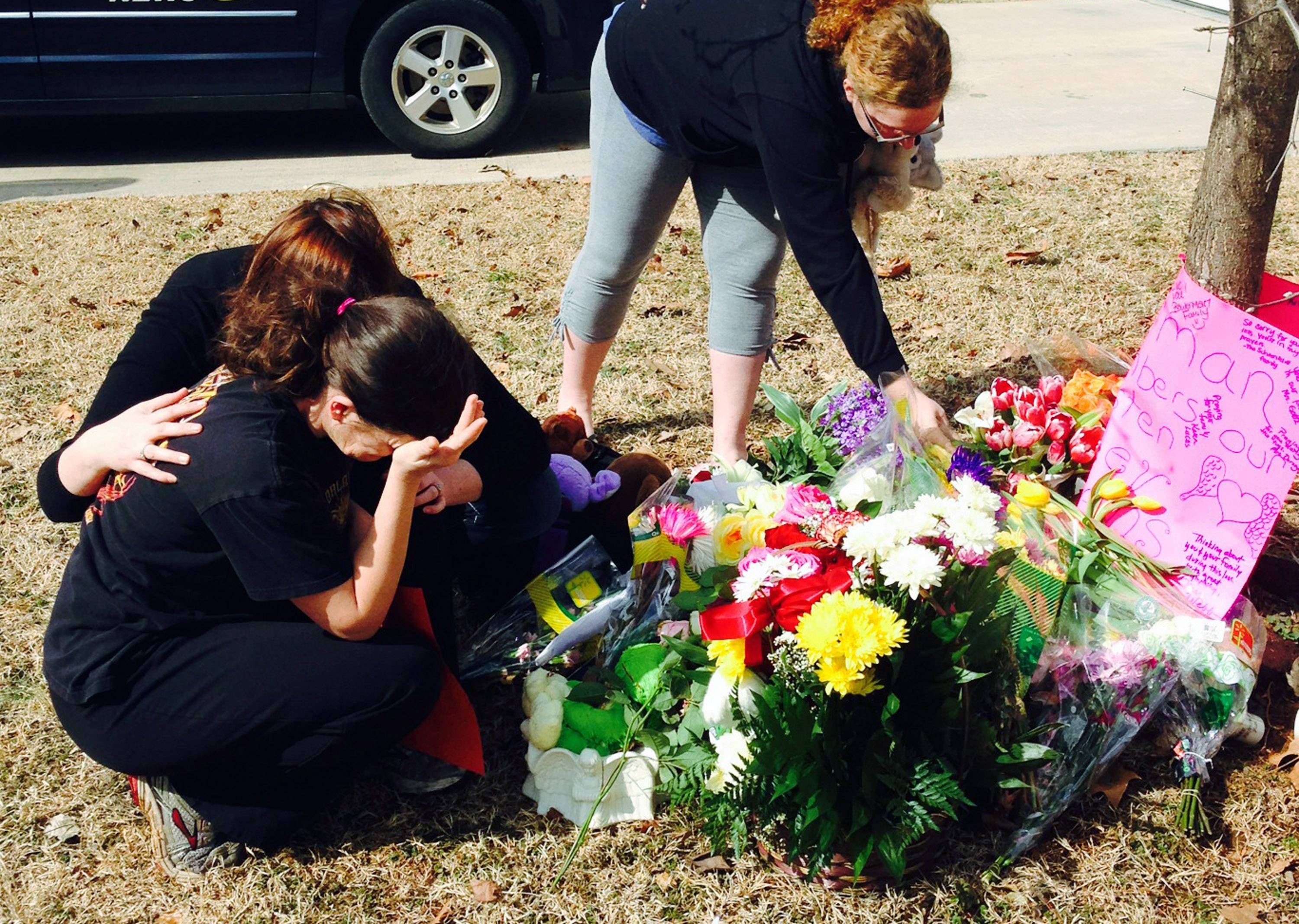 Stacey Owens, front left, mother of Hailey Owens, is consoled by Sara Wells, left, as family member Teri Nord arranges flowers left by well wishers Thursday, Feb. 20, 2014 near the site where the 10-year-old girl was abducted just blocks from her Springfield, Mo., home. Prosecutors have charged Craig Michael Wood with first-degree murder, kidnapping and armed criminal action in the girl's death.
