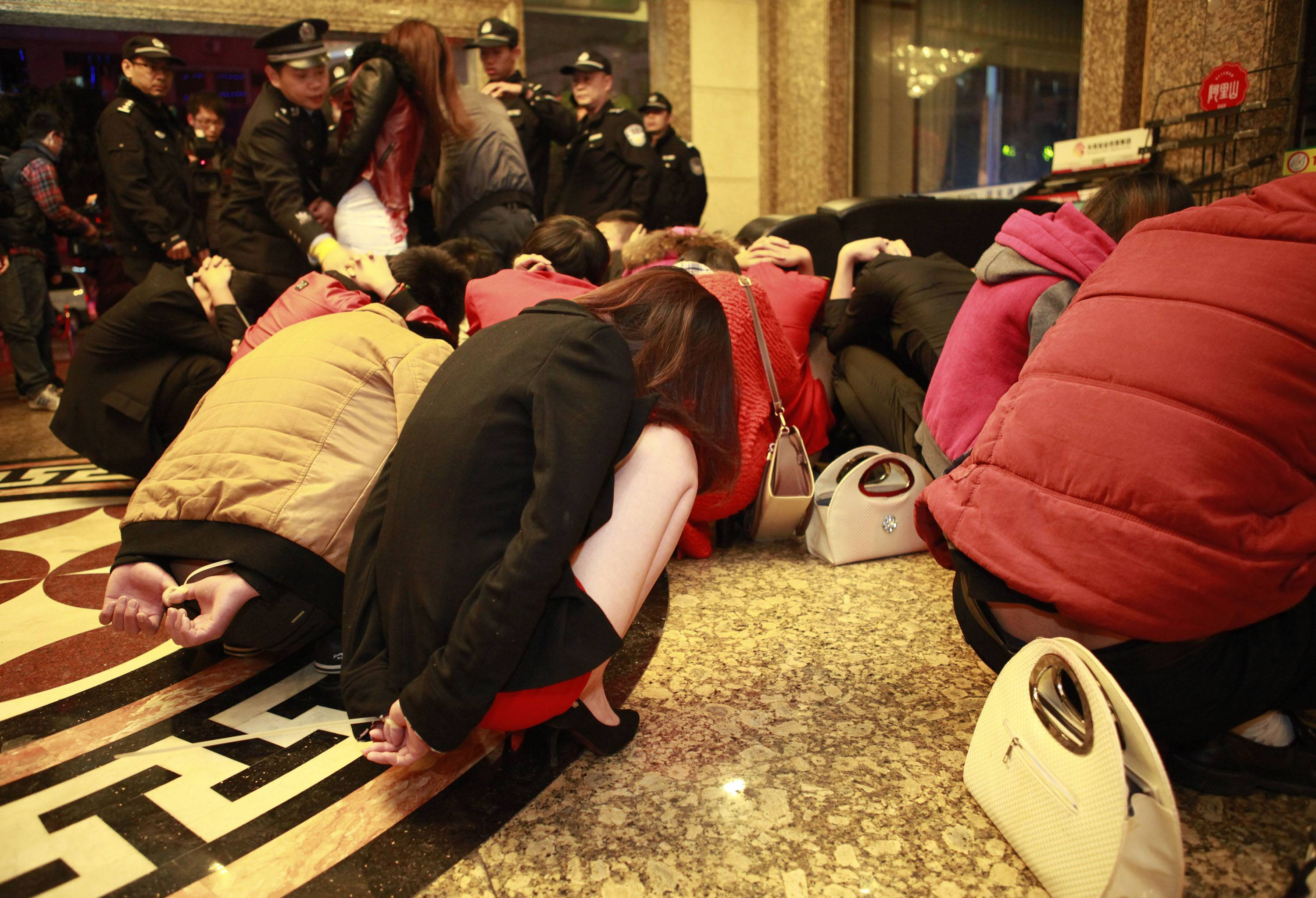 Detained suspects are gathered in a lobby during an anti-prostitution raid at a hotel in Dongguan in south China's Guangdong province. China's booming sex industry may finally be entering a winter after decades of robust growth, as Beijing wages a harsher-than-usual clampdown on vice.