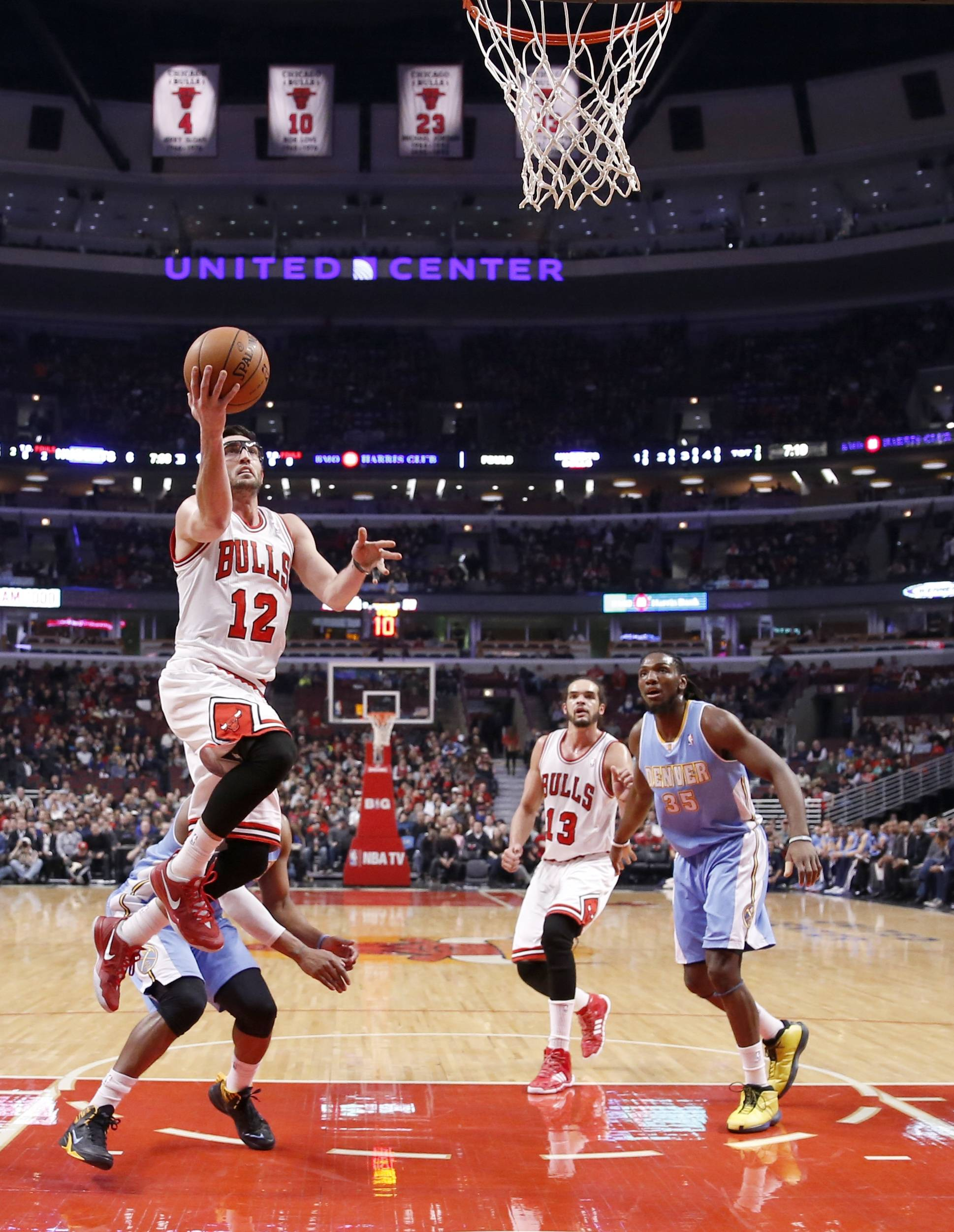 Bulls guard Kirk Hinrich scores past Denver Nuggets guard Randy Foye as the Bulls' Joakim Noah and Denver's Kenneth Faried watch during the first half of Friday's game in Chicago.